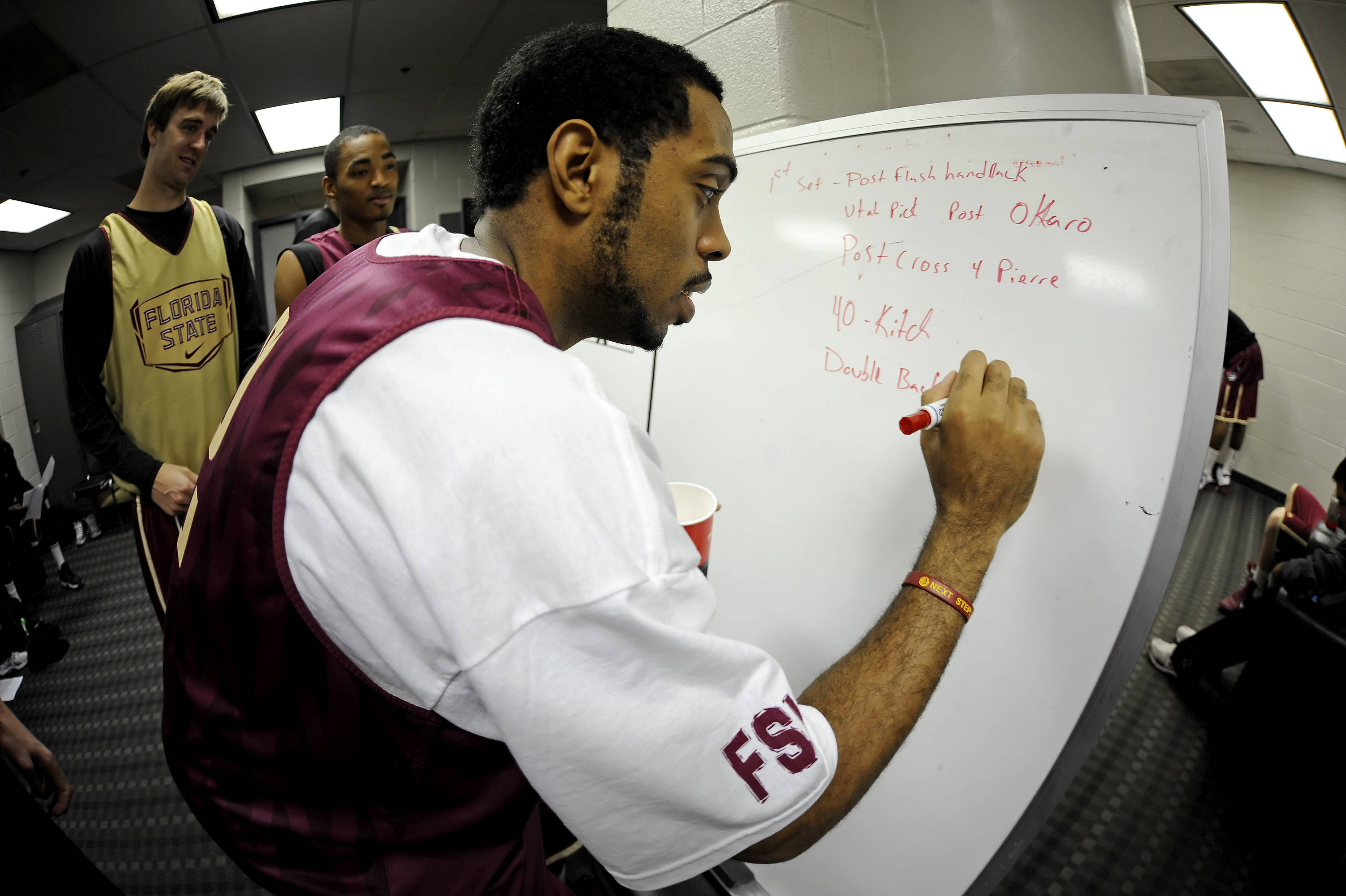 Derwin Kitchen writes on the white board in the locker room