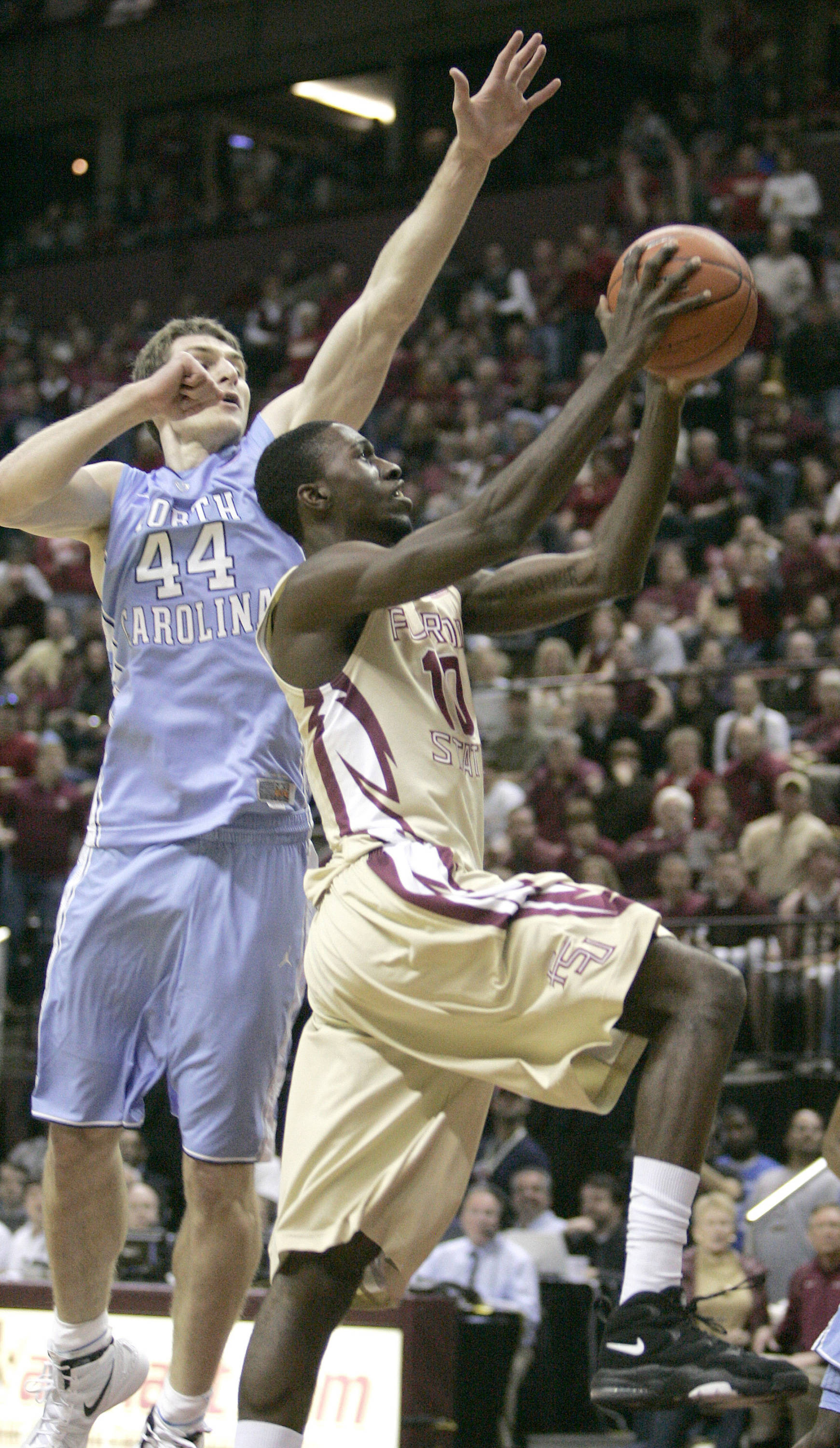 Florida State's Okaro White pushes past past the defense of North Carolina's Tyler Zeller (44) to attempt a shot in the first half of an NCAA college basketball game on Saturday, Jan. 14, 2012, in Tallahassee, Fla.(AP Photo/Steve Cannon)