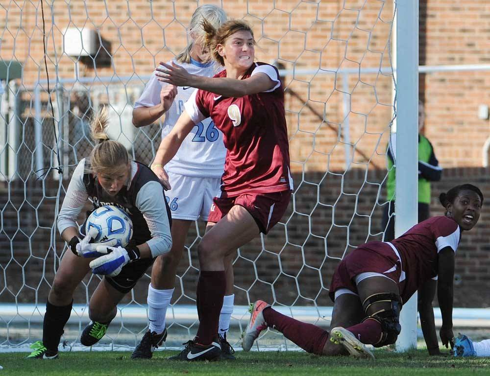 Florida State's Kassey Kallman (9) reacts to the ball crossing into the goal as North Carolina goalkeeper Anna Sieloff tries to make the save.  Jessica Price looks on after scoring the game-winner