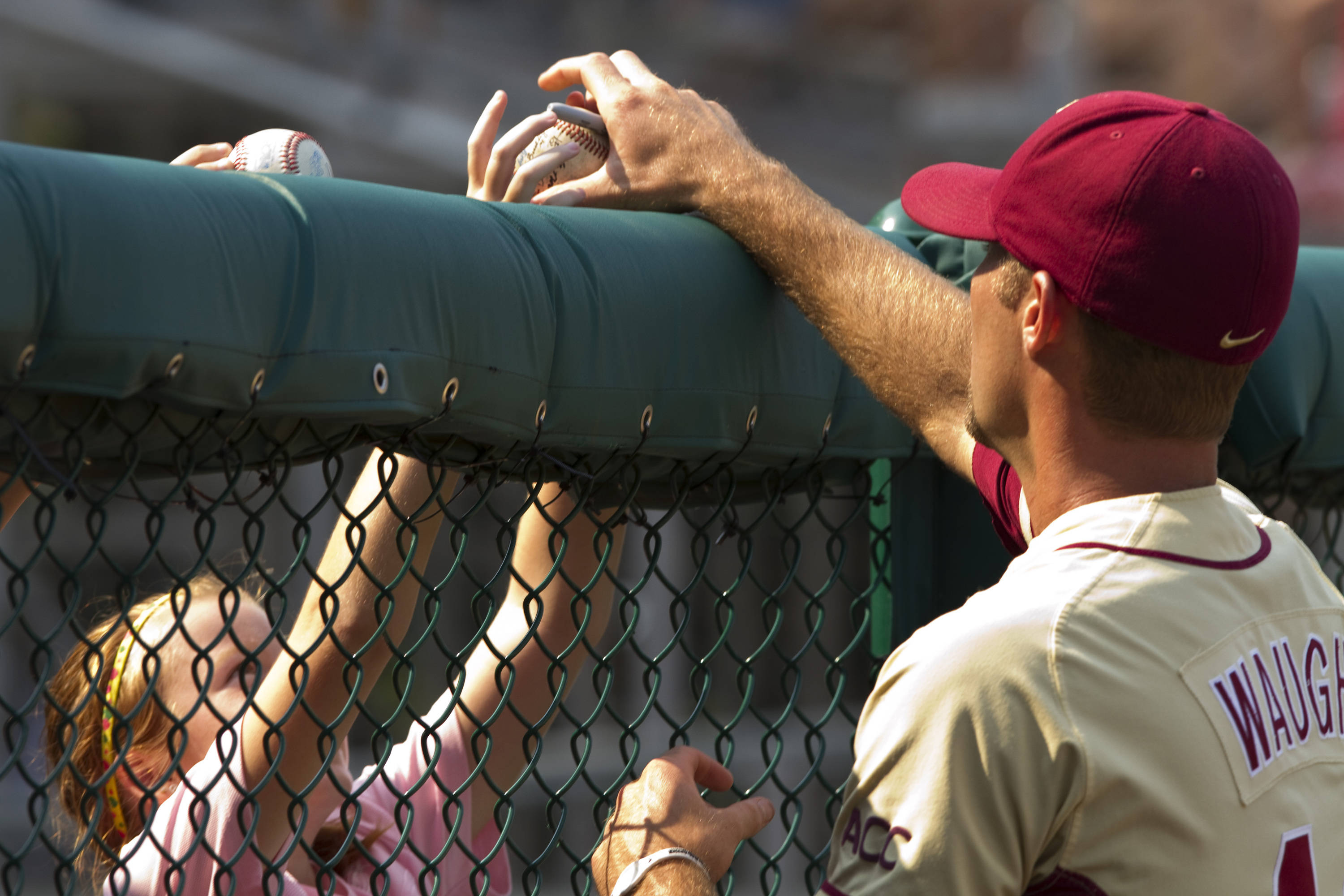 Mack Waugh (44) autographs a baseball for a young fan.