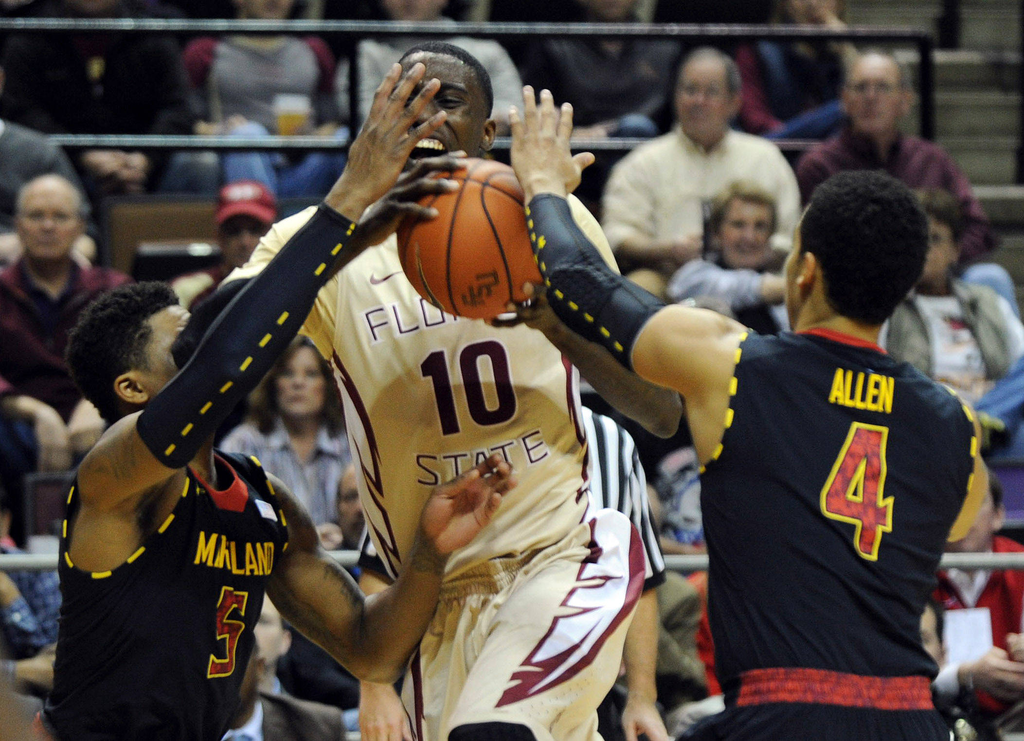 Jan 12, 2014; Tallahassee, FL, USA; Florida State Seminoles forward Okaro White (10) is fouled as he is defended by Maryland Terrapins guard Seth Allen (4) and guard Nick Faust (5) during the first half at Donald L. Tucker Center. Mandatory Credit: Melina Vastola-USA TODAY Sports