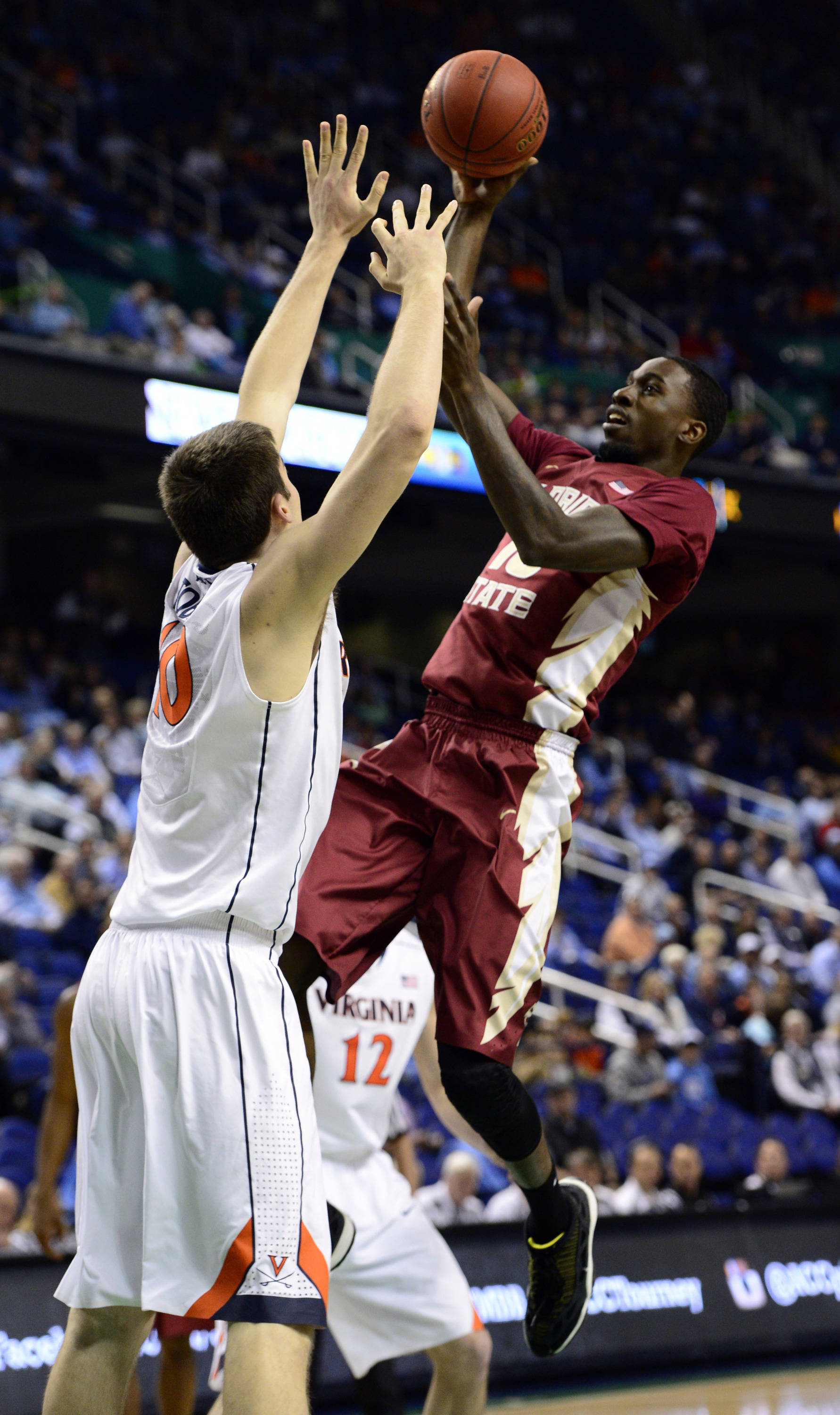 Mar 14, 2014; Greensboro, NC, USA;  Florida State Seminoles forward Okaro White (10) goes up for a shot over Virginia Cavaliers forward/center Mike Tobey (10) in the quarterfinals of the ACC college basketball tournament at Greensboro Coliseum. Mandatory Credit: John David Mercer-USA TODAY Sports