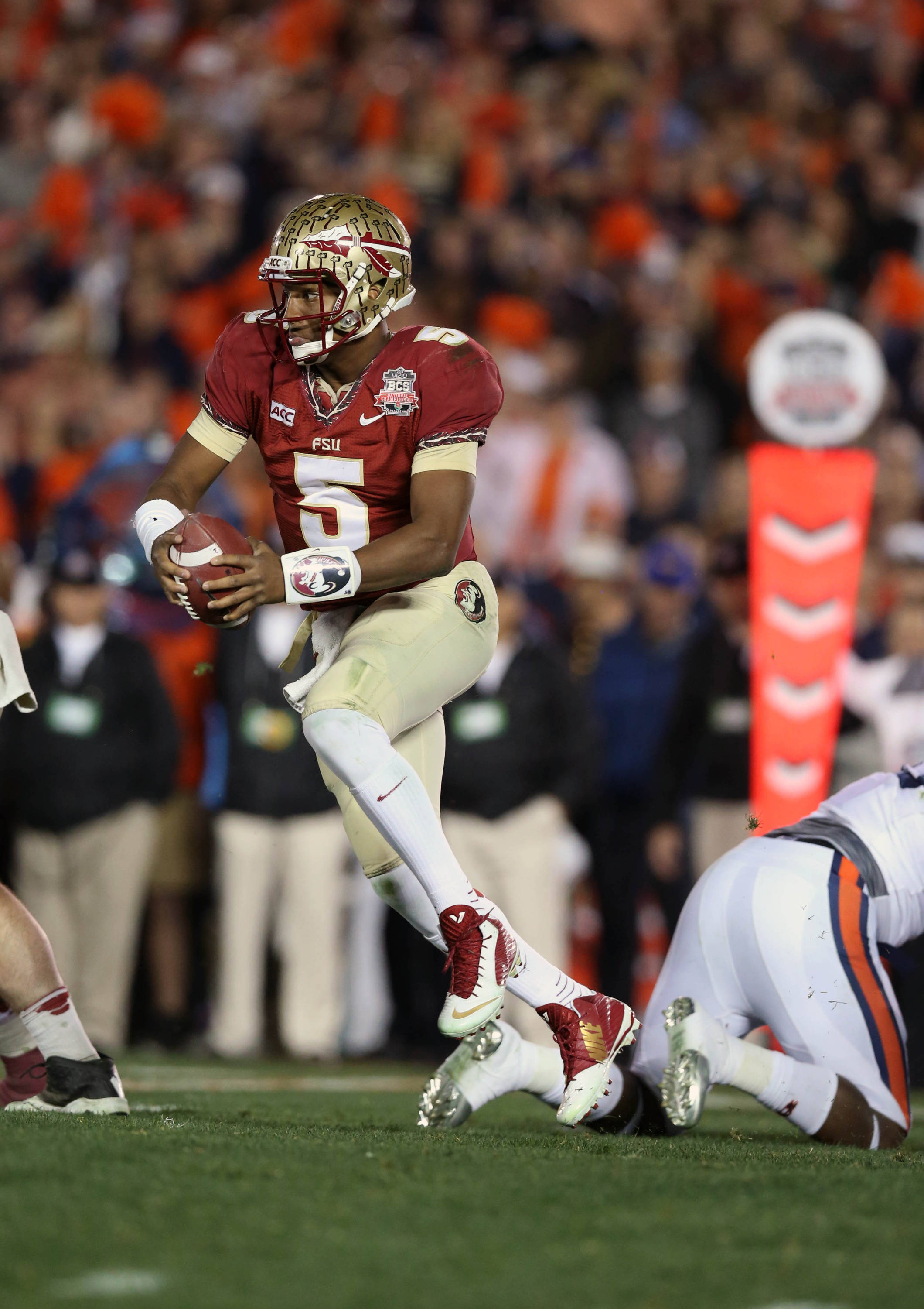 Jan 6, 2014; Pasadena, CA, USA; Florida State Seminoles quarterback Jameis Winston (5) carries the ball against the Auburn Tigers during the first half of the 2014 BCS National Championship game at the Rose Bowl.  Mandatory Credit: Matthew Emmons-USA TODAY Sports