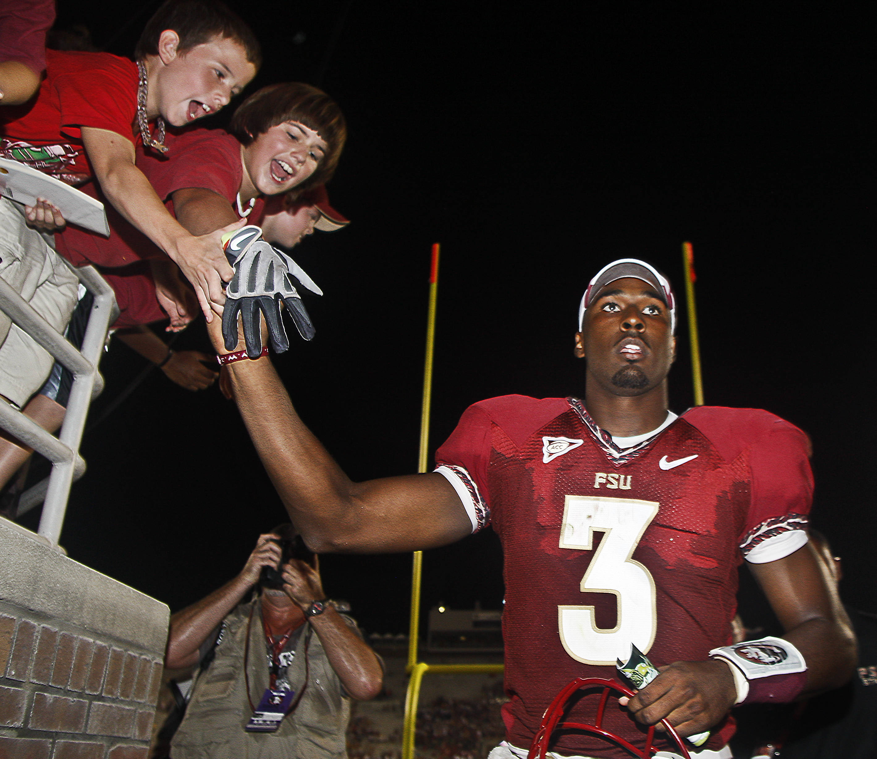 Florida State quarterback E.J. Manuel (3) gives away his glove to a fan as he leaves after an NCAA college football game against Charleston Southern on Saturday, Sept. 10, 2011, in Tallahassee, Fla. FSU won 62-10. (AP Photo/Phil Sears)