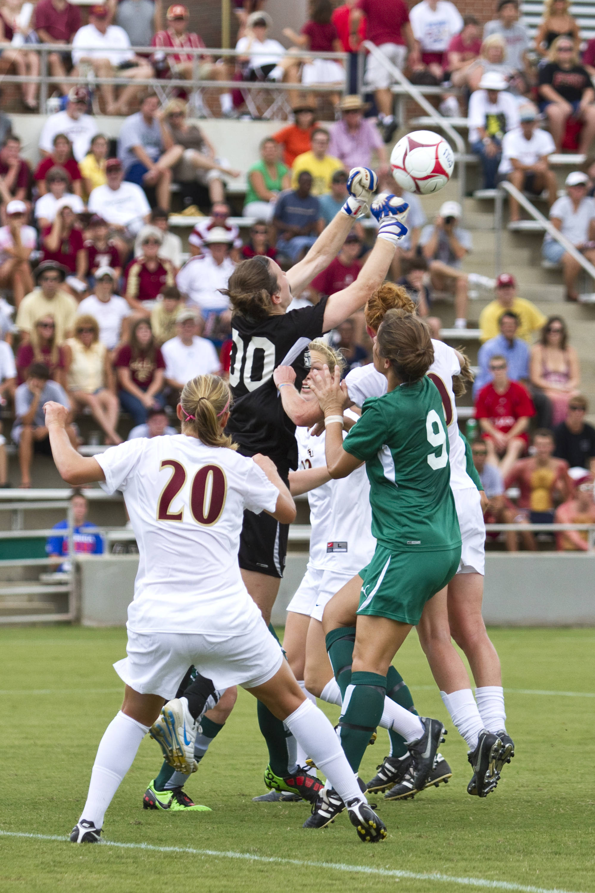 Janice Cayman (20), Tori Huster (10), and Ella Stephan (17) attempt to head the ball over the keeper from Stetson.