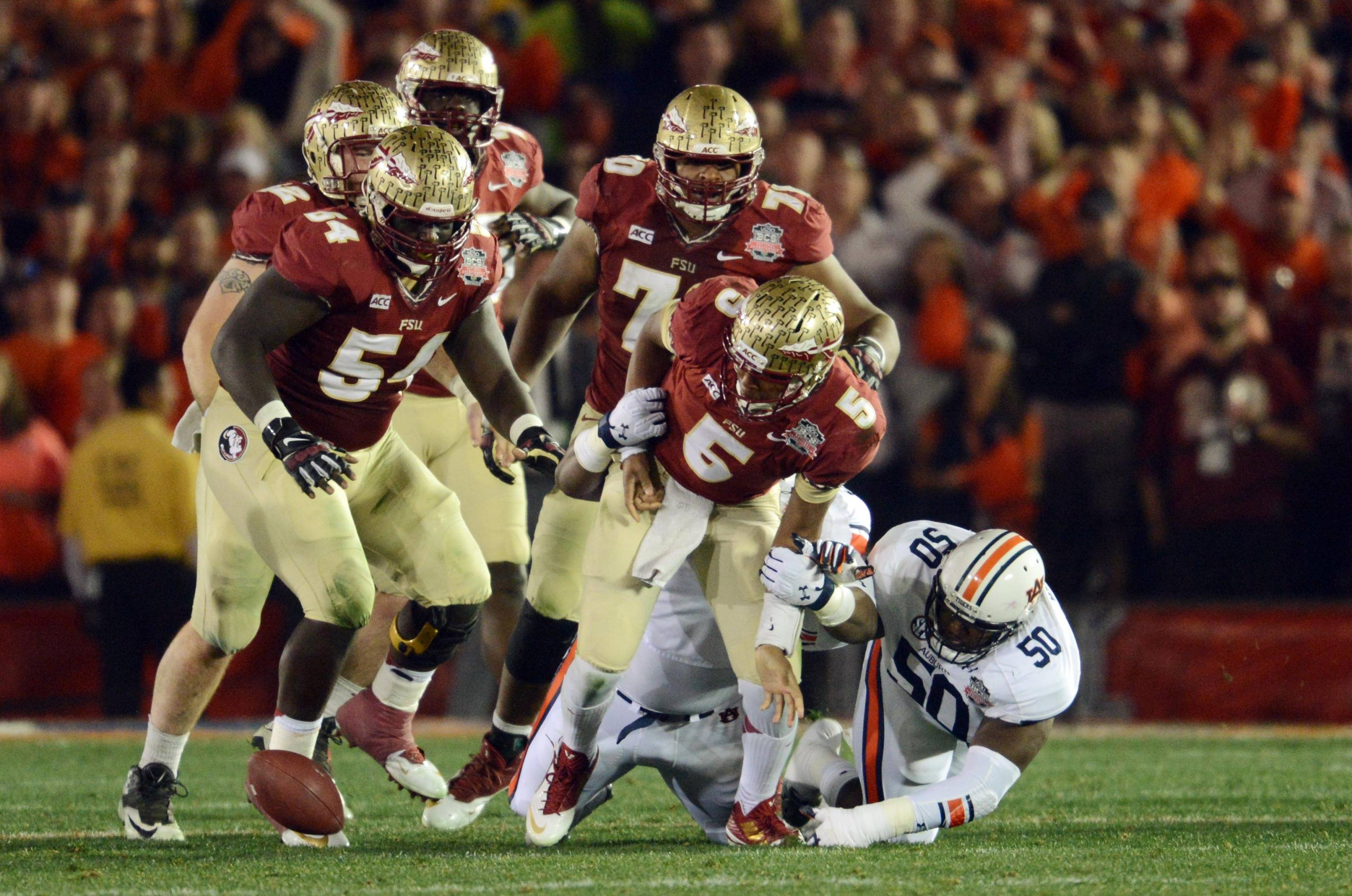 Jan 6, 2014; Pasadena, CA, USA; Florida State Seminoles quarterback Jameis Winston (5) fumbles the ball as Auburn Tigers defensive tackle Ben Bradley (50) closes in for the tackle during the first half of the 2014 BCS National Championship game at the Rose Bowl.  Mandatory Credit: Jayne Kamin-Oncea-USA TODAY Sports