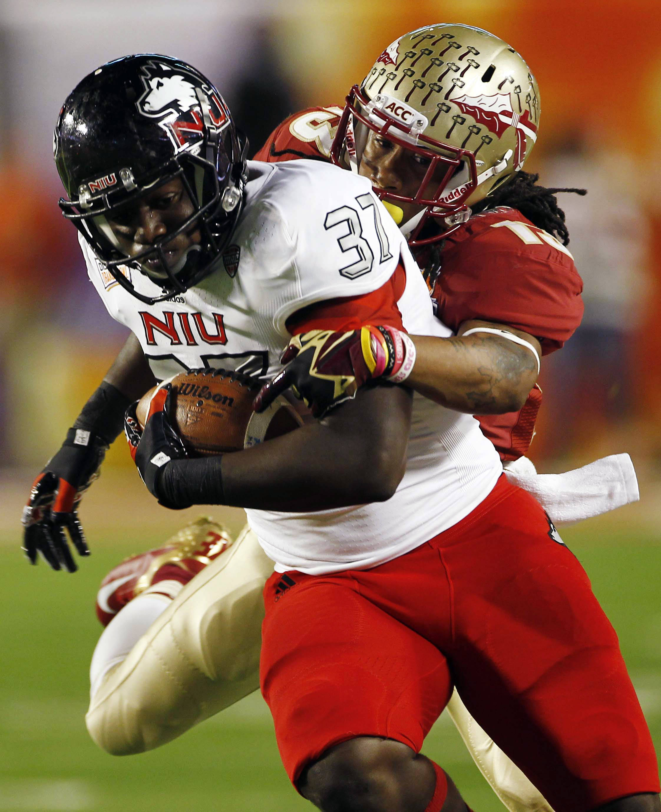 Northern Illinois tight end Desroy Maxwell (37) is tackled by Florida State defensive back Ronald Darby (13) during the first half of the Orange Bowl NCAA college football game, Tuesday, Jan. 1, 2013, in Miami. (AP Photo/J Pat Carter)