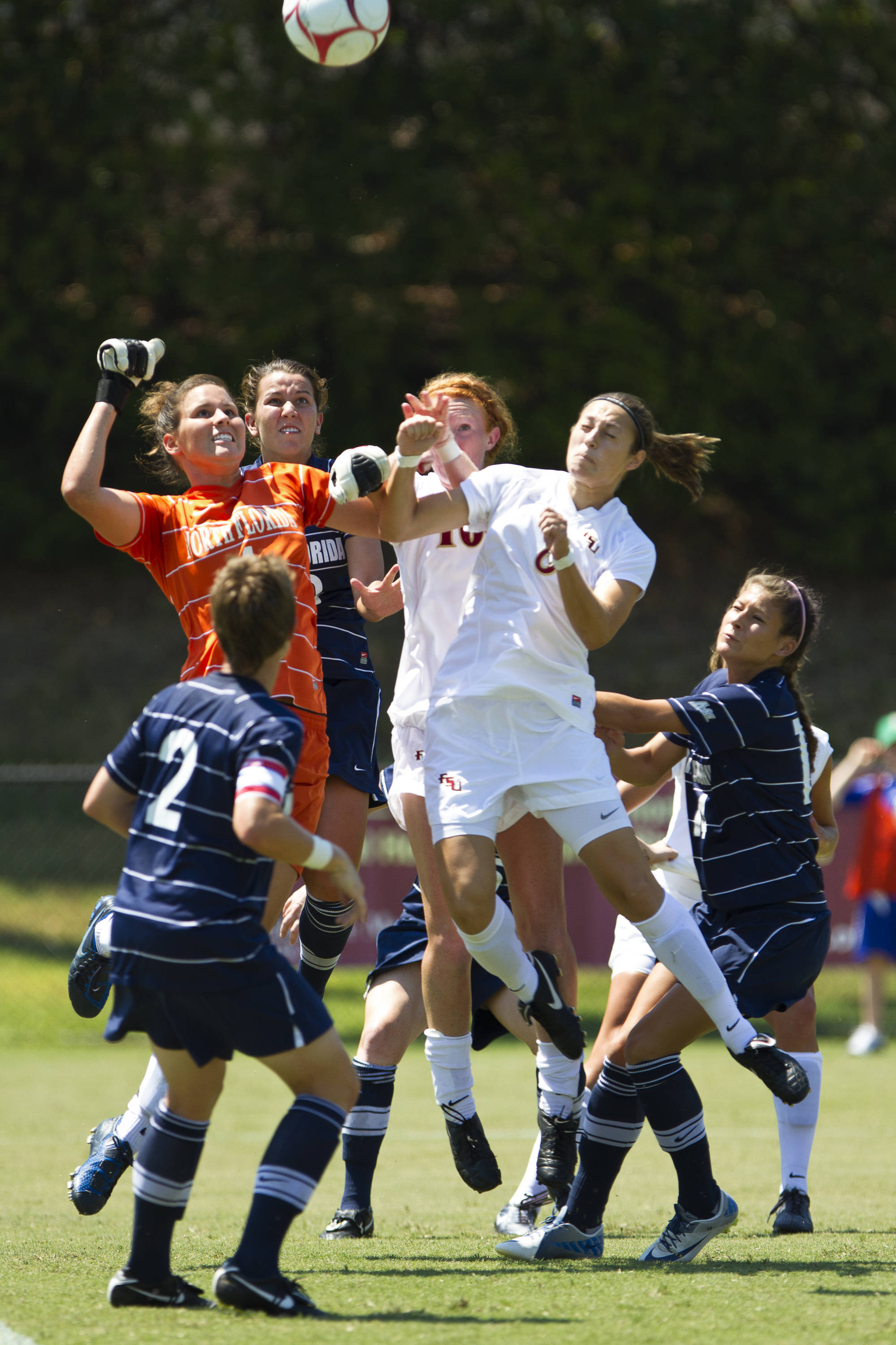 Katya Gokhman (8) and Tori Huster (10) challenge the keeper from North Florida for a ball in Sunday's game.