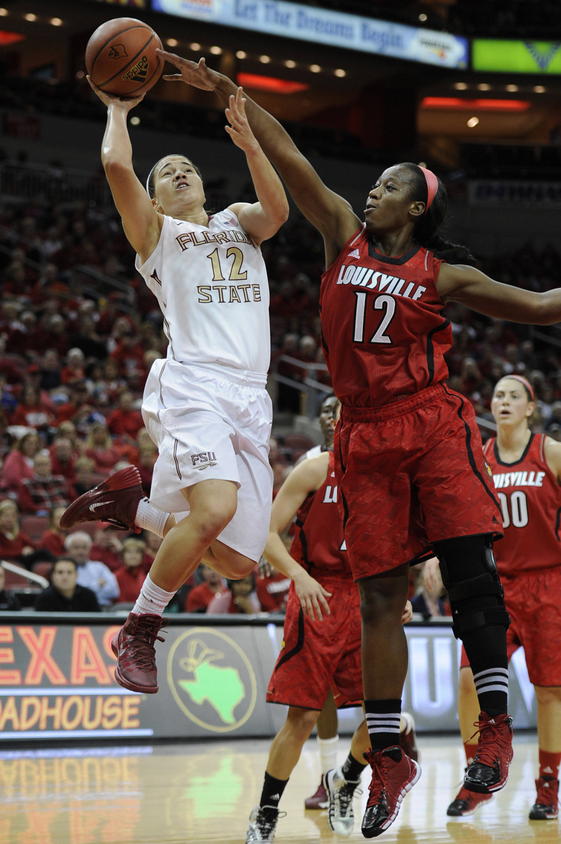 Nov 24, 2013; Louisville, KY, USA; Florida State Seminoles guard Brittany Brown (12) shoots the ball in front of Louisville Cardinals forward Shawnta' Dyer (12) during the first half at KFC YUM! Center. Mandatory Credit: Jamie Rhodes-USA TODAY Sports