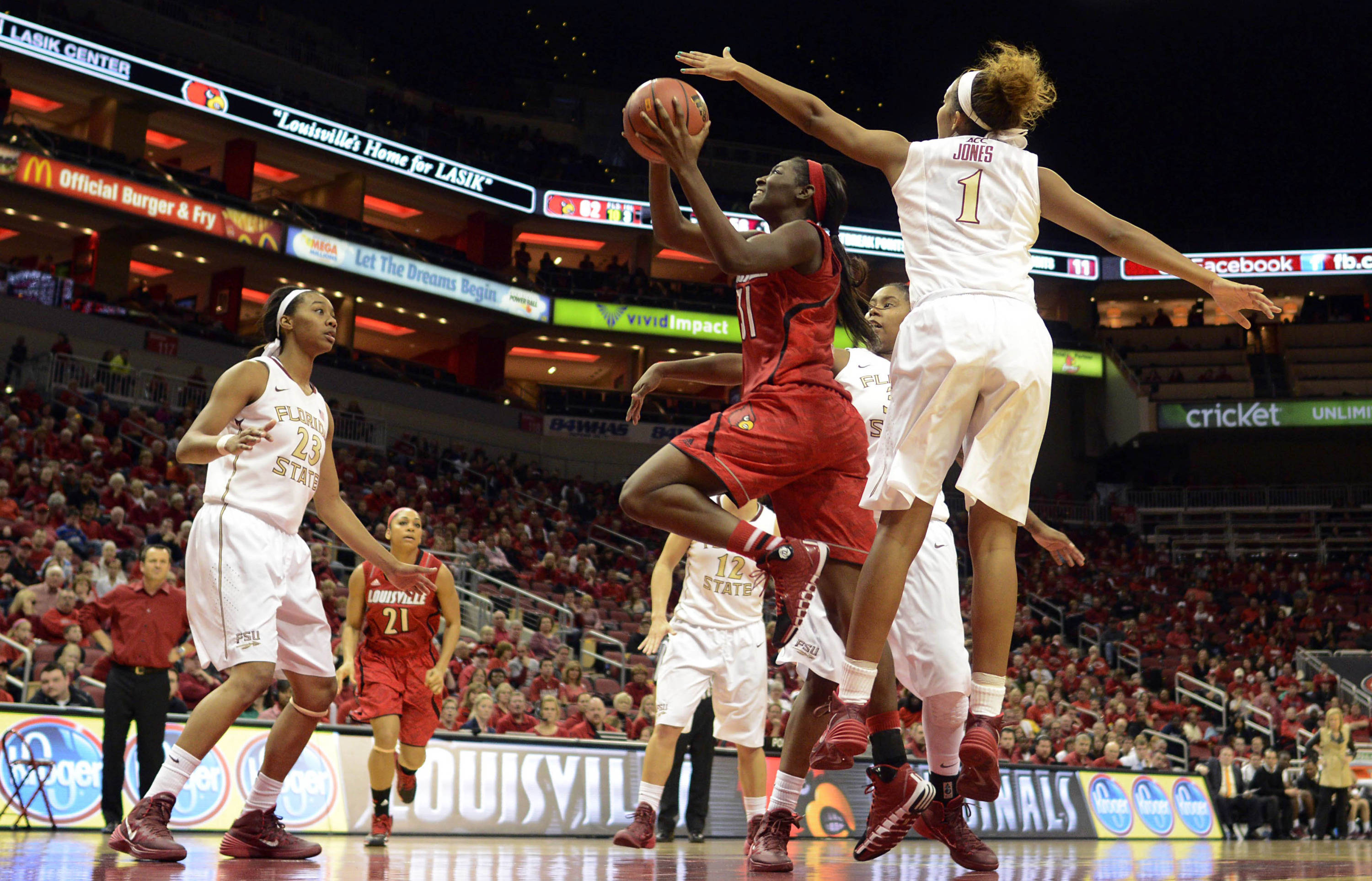 Nov 24, 2013; Louisville, KY, USA; Louisville Cardinals forward Asia Taylor (31) shoots against Florida State Seminoles guard Morgan Jones (1) during overtime during the second half at KFC YUM! Center. Louisville defeated Florida State 69-59.  Mandatory Credit: Jamie Rhodes-USA TODAY Sports