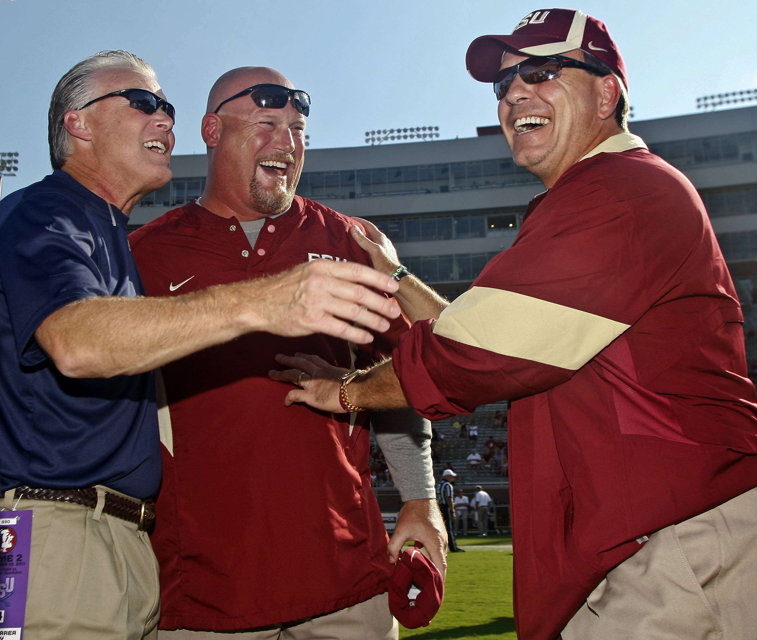 Charleston Southern head coach Jay Mills, left, laughs with Florida State linebackers coach Greg Hudson and head coach Jimbo Fisher, right, prior to the start of an NCAA college football game on Saturday, Sept. 10, 2011, in Tallahassee, Fla. (AP Photo/Phil Sears)