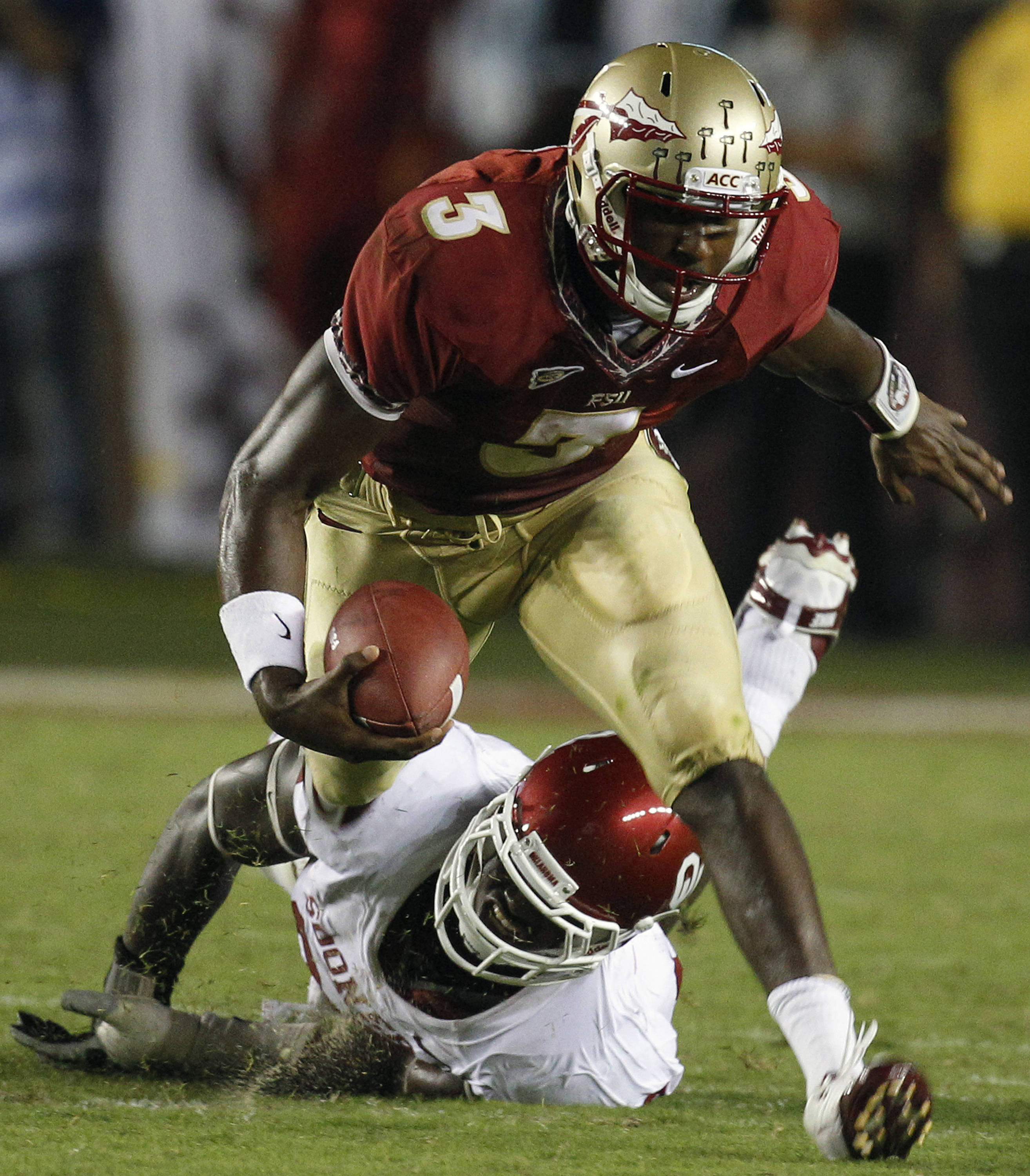 Florida State quarterback EJ Manuel (3) is tripped up by Oklahoma defensive end David King (90) on a second quarter run. (AP Photo/Chris O'Meara)