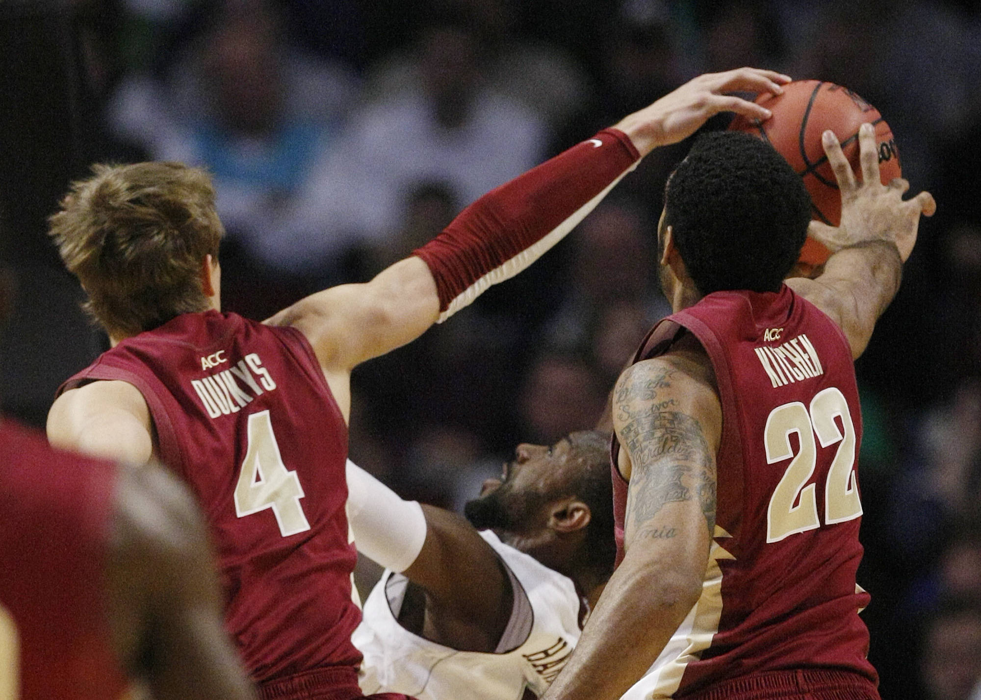 Florida State defenders Deividas Dulkys of Lithuania and Derwin Kitchen combine to block a shot by Texas A&M's Dash Harris in the first half. (AP Photo/Charles Rex Arbogast)