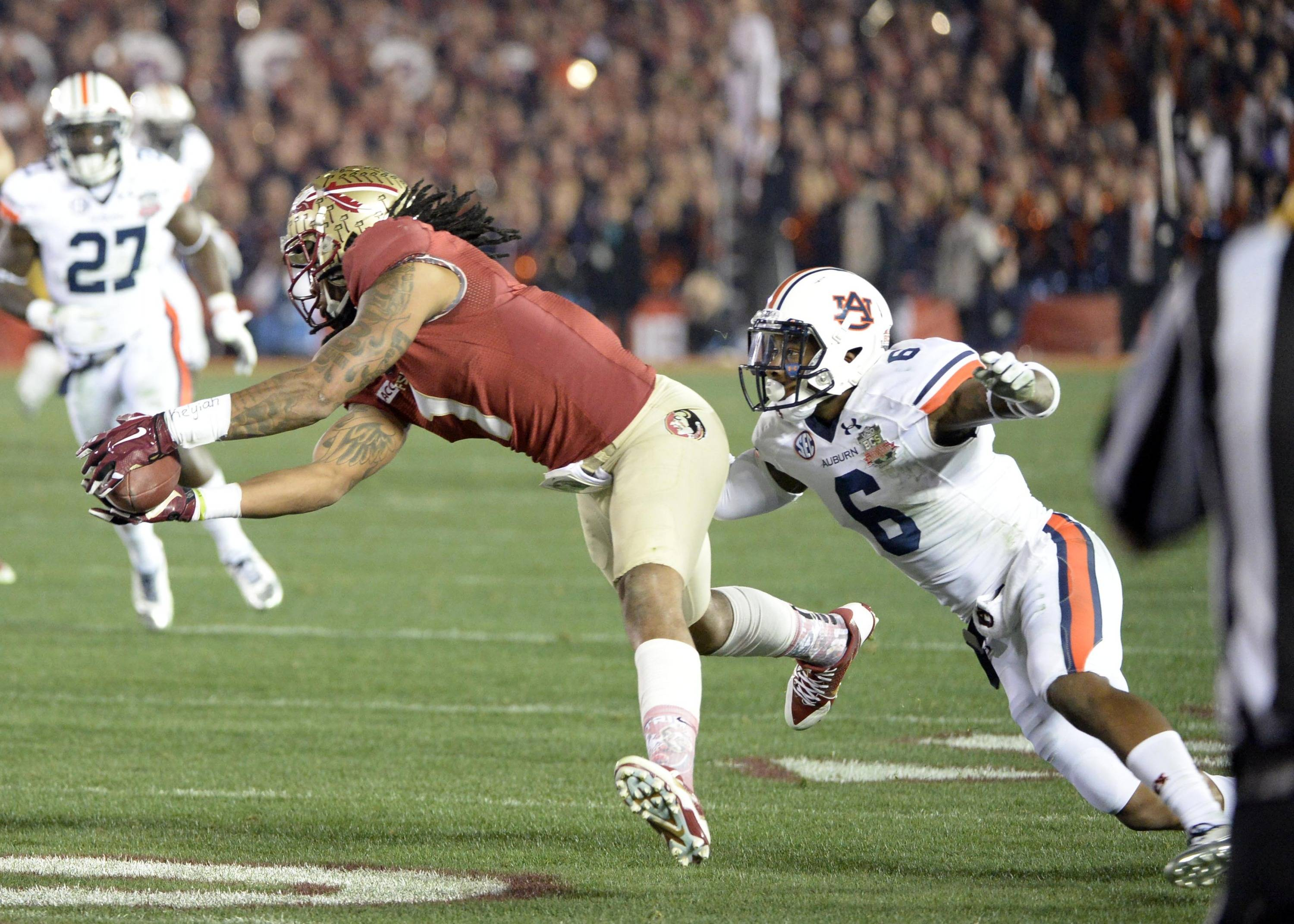 Jan 6, 2014; Pasadena, CA, USA; Florida State Seminoles wide receiver Kelvin Benjamin (1) makes a catch under pressure from Auburn Tigers defensive back Jonathon Mincy (6) during the second half of the 2014 BCS National Championship game at the Rose Bowl.  Mandatory Credit: Richard Mackson-USA TODAY Sports