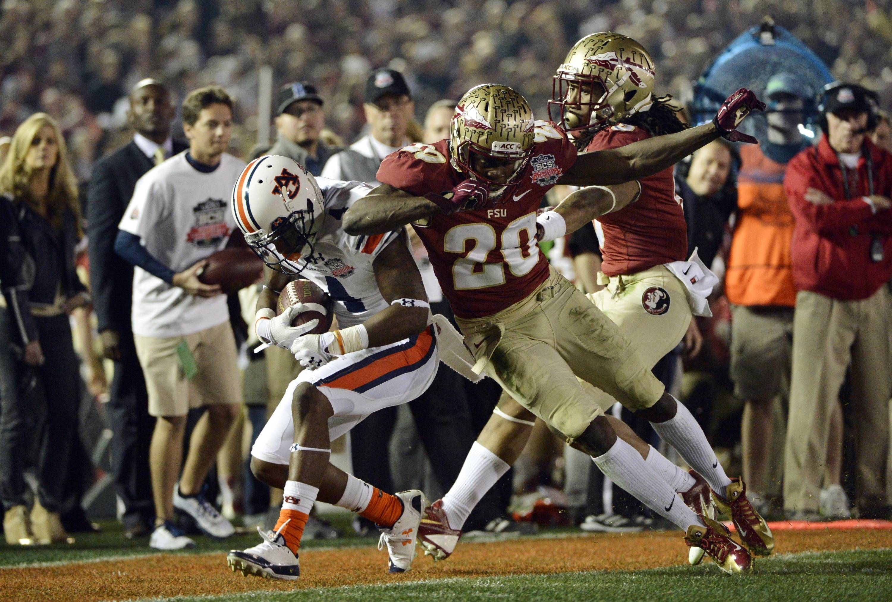 Jan 6, 2014; Pasadena, CA, USA; Auburn Tigers wide receiver Quan Bray (4) is tackled by Florida State Seminoles defensive back Lamarcus Joyner (20) during the first half of the 2014 BCS National Championship game at the Rose Bowl.  Mandatory Credit: Robert Hanashiro-USA TODAY Sports