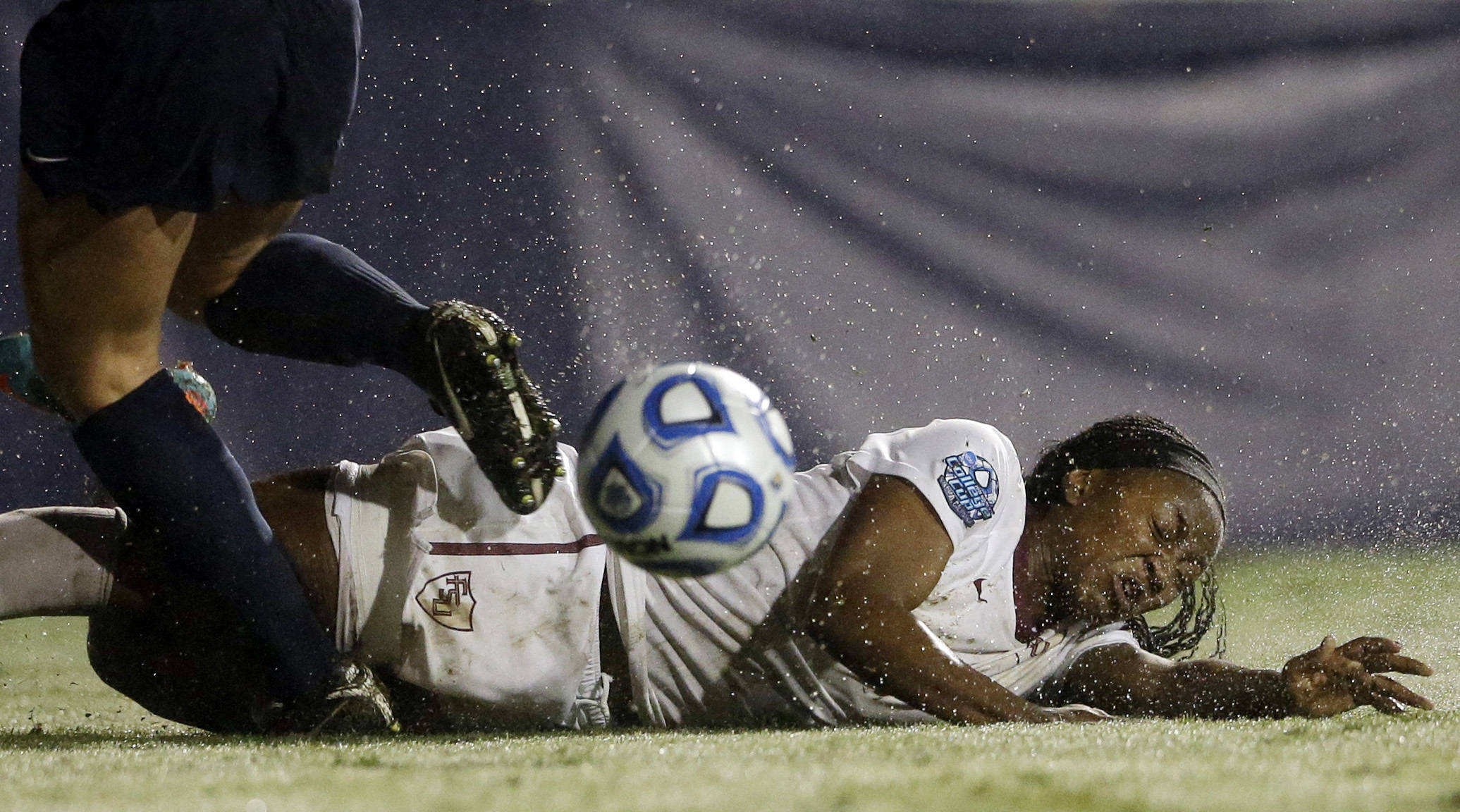 Jamia Fields slips on the wet field during the second half. (AP Photo/Gregory Bull)