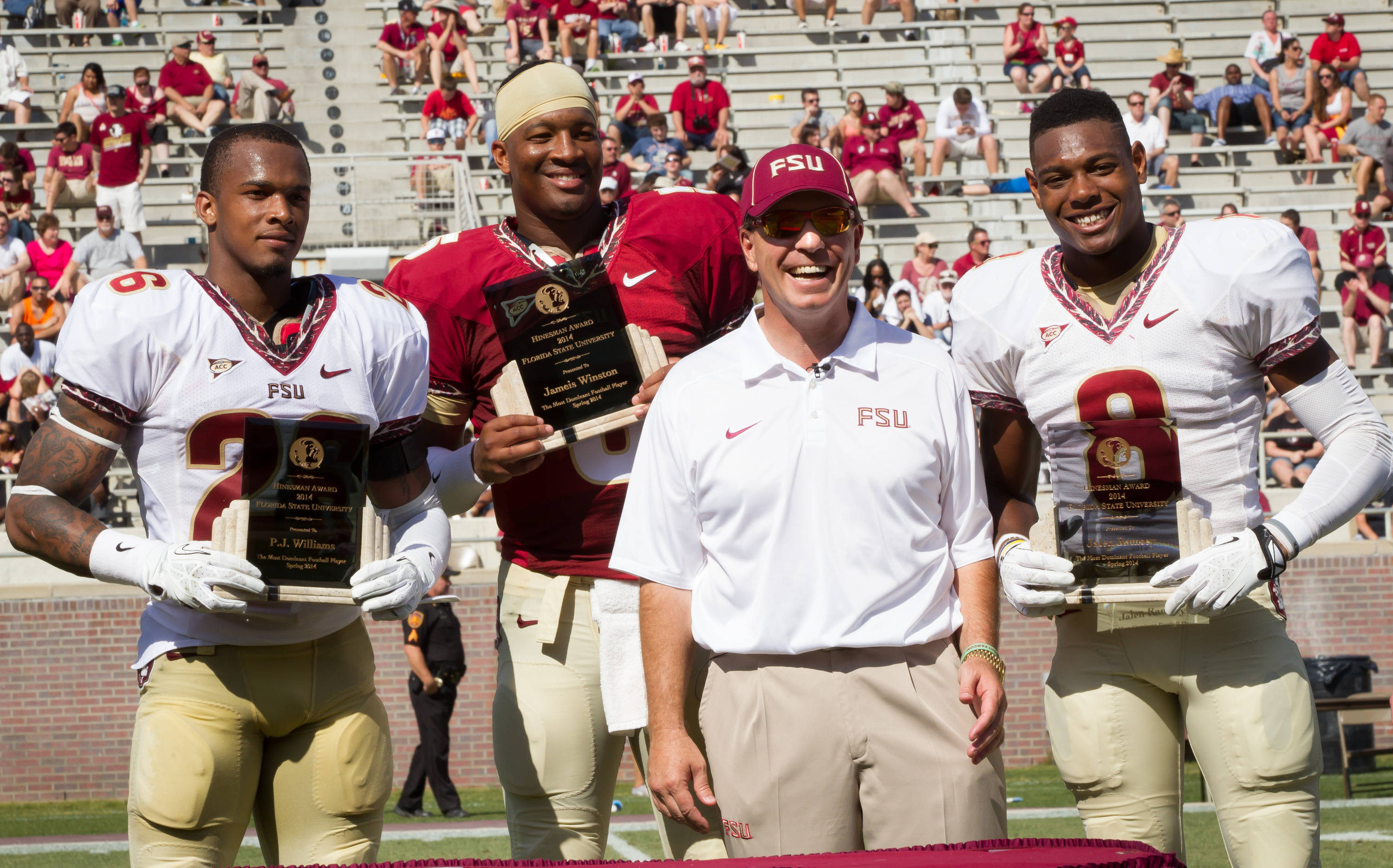 P.J. Williams (26), Jameis Winston (5), Jalen Ramsey (8) are presented the Hinesman Award from Jimbo Fisher.