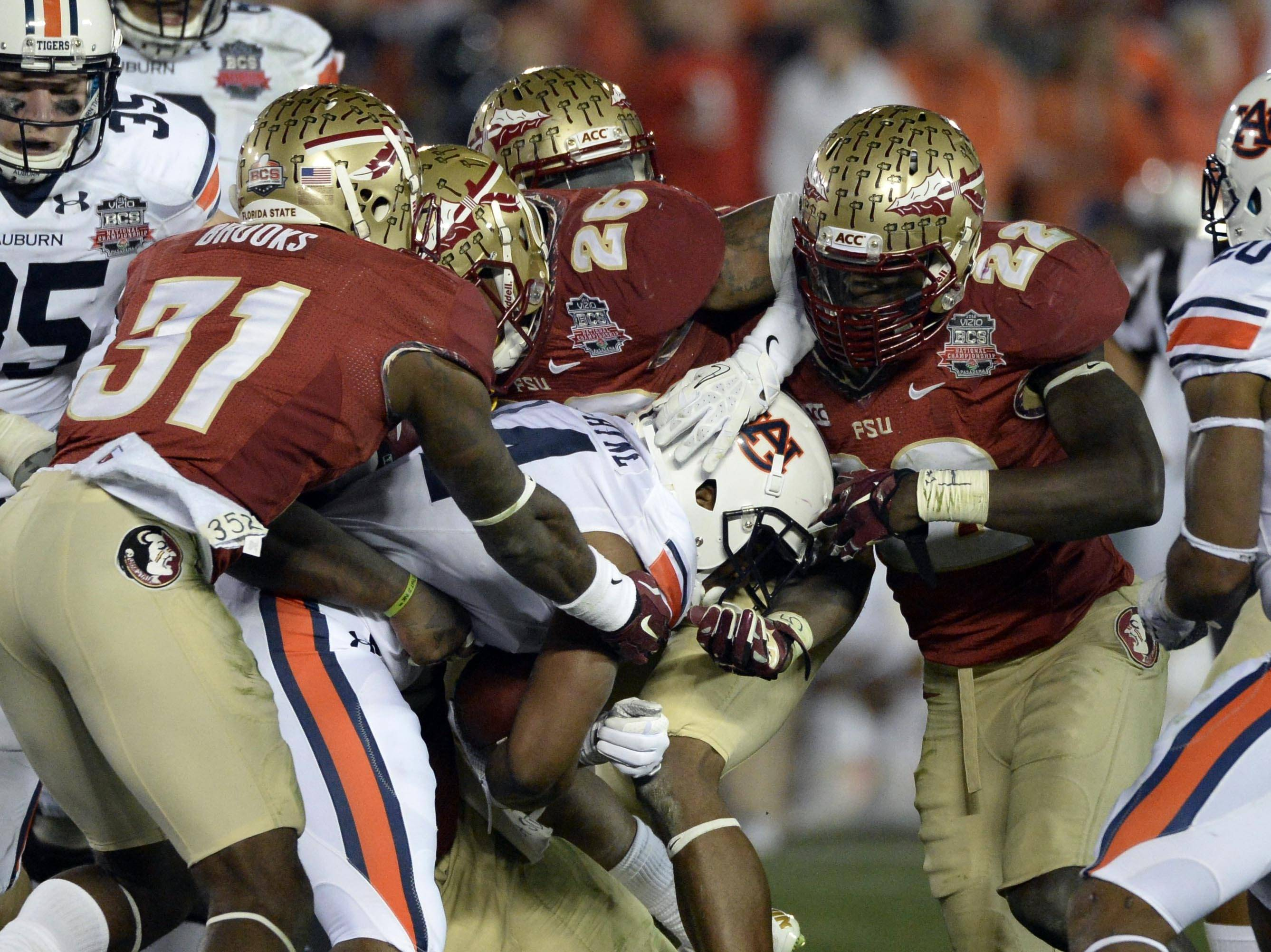 Jan 6, 2014; Pasadena, CA, USA; Florida State Seminoles linebacker Telvin Smith (22) and defensive back Terrence Brooks (31) and defensive back P.J. Williams (26) tackle Auburn Tigers running back Cameron Artis-Payne (44) during the second half of the 2014 BCS National Championship game at the Rose Bowl.  Mandatory Credit: Richard Mackson-USA TODAY Sports
