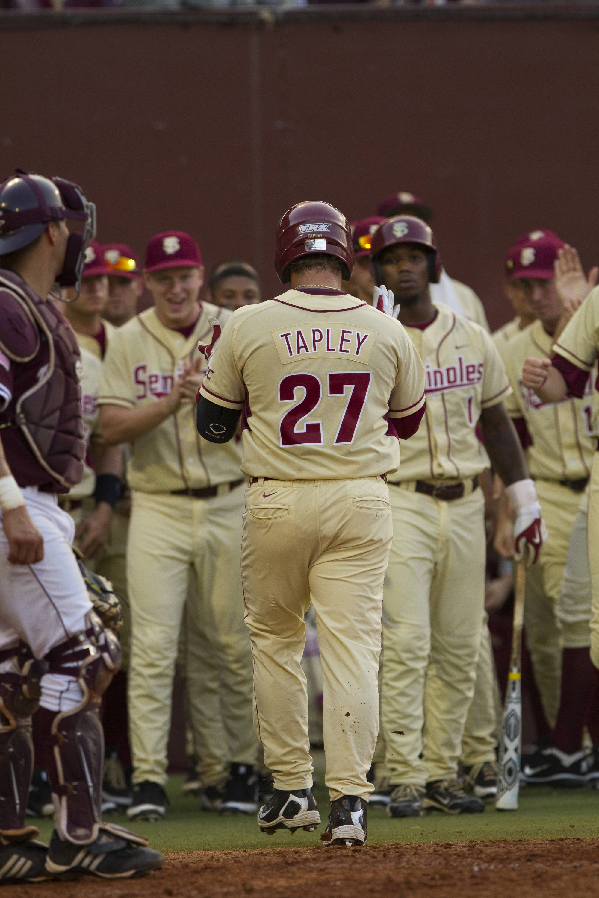 Stuart Tapley (27) is congratulated by teammates after scoring a run.