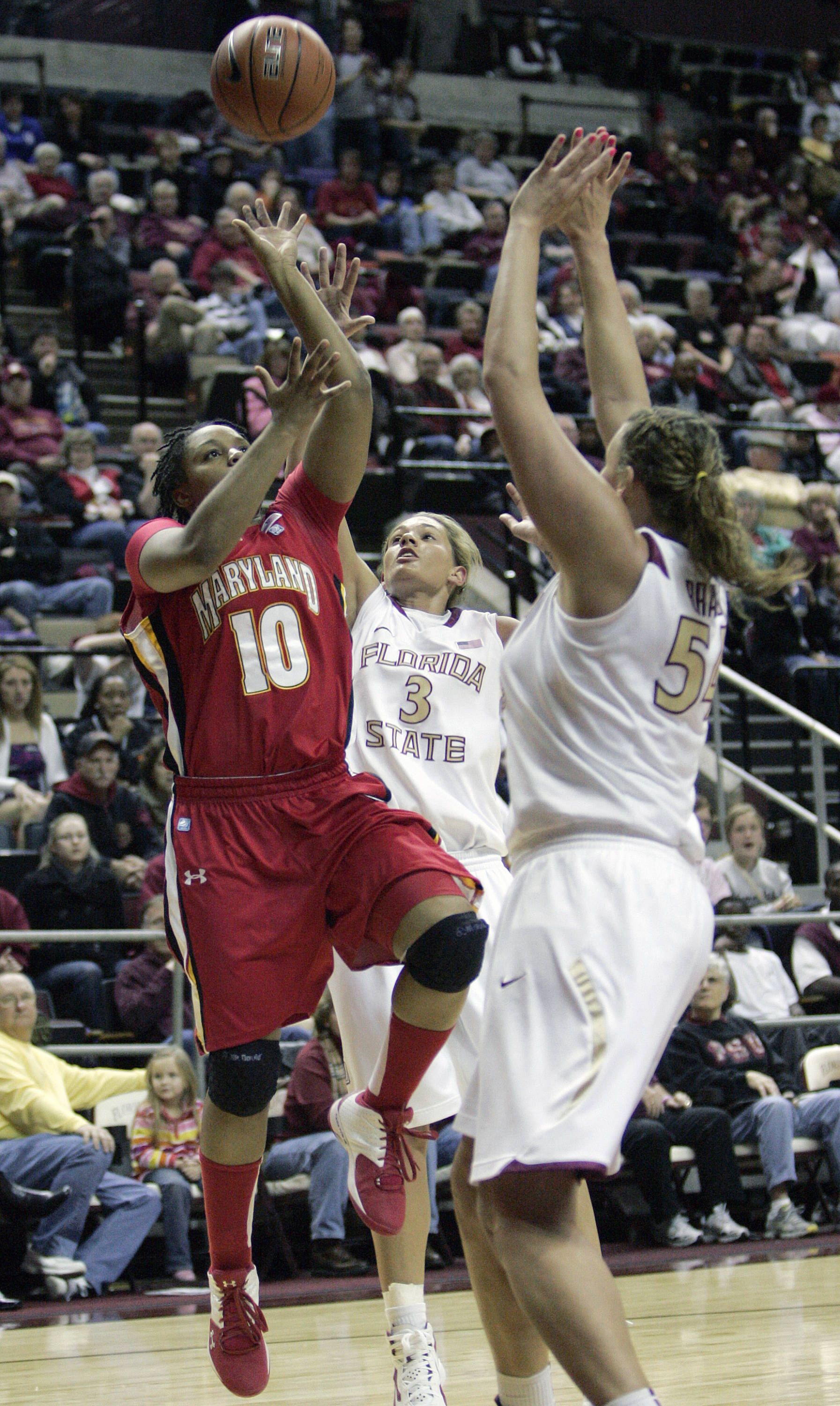 Maryland's Anjale Barrett gets a shot past the defense of Florida State's Alexa Deluzio, center and Cierra Bravard in the first half of an NCAA  college basketball game on Monday, Jan. 2, 2012 in Tallahassee, Fla.(AP Photo/Steve Cannon)
