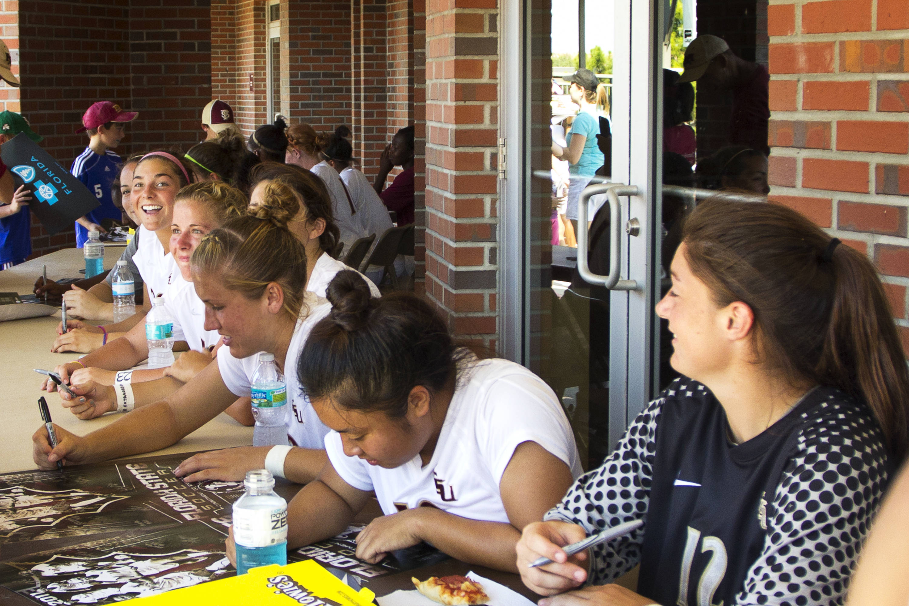 The team autographs posters for fans following the game against North Florida on August 28, 2011.
