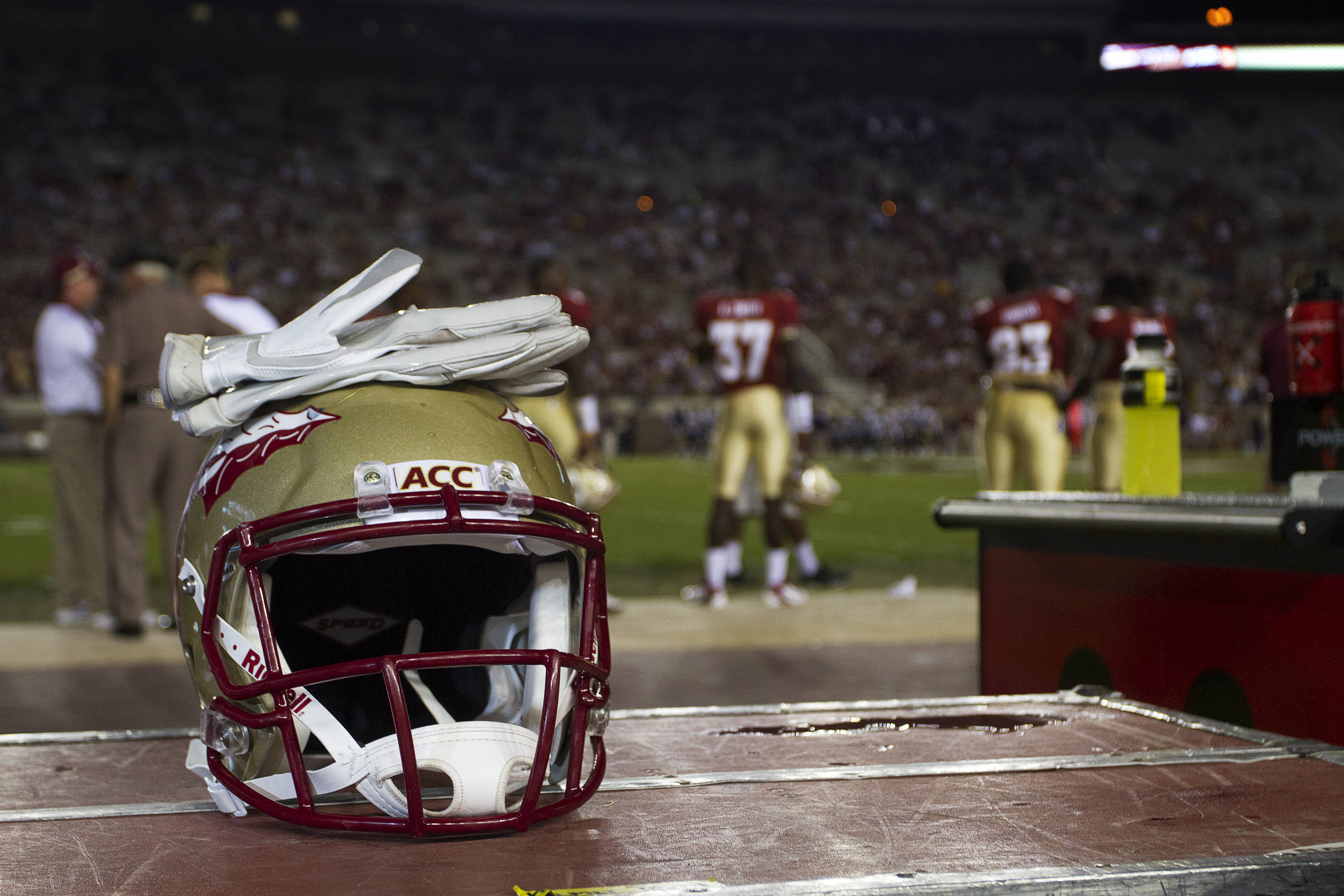 A helmet and gloves sit on the Seminole sideline.