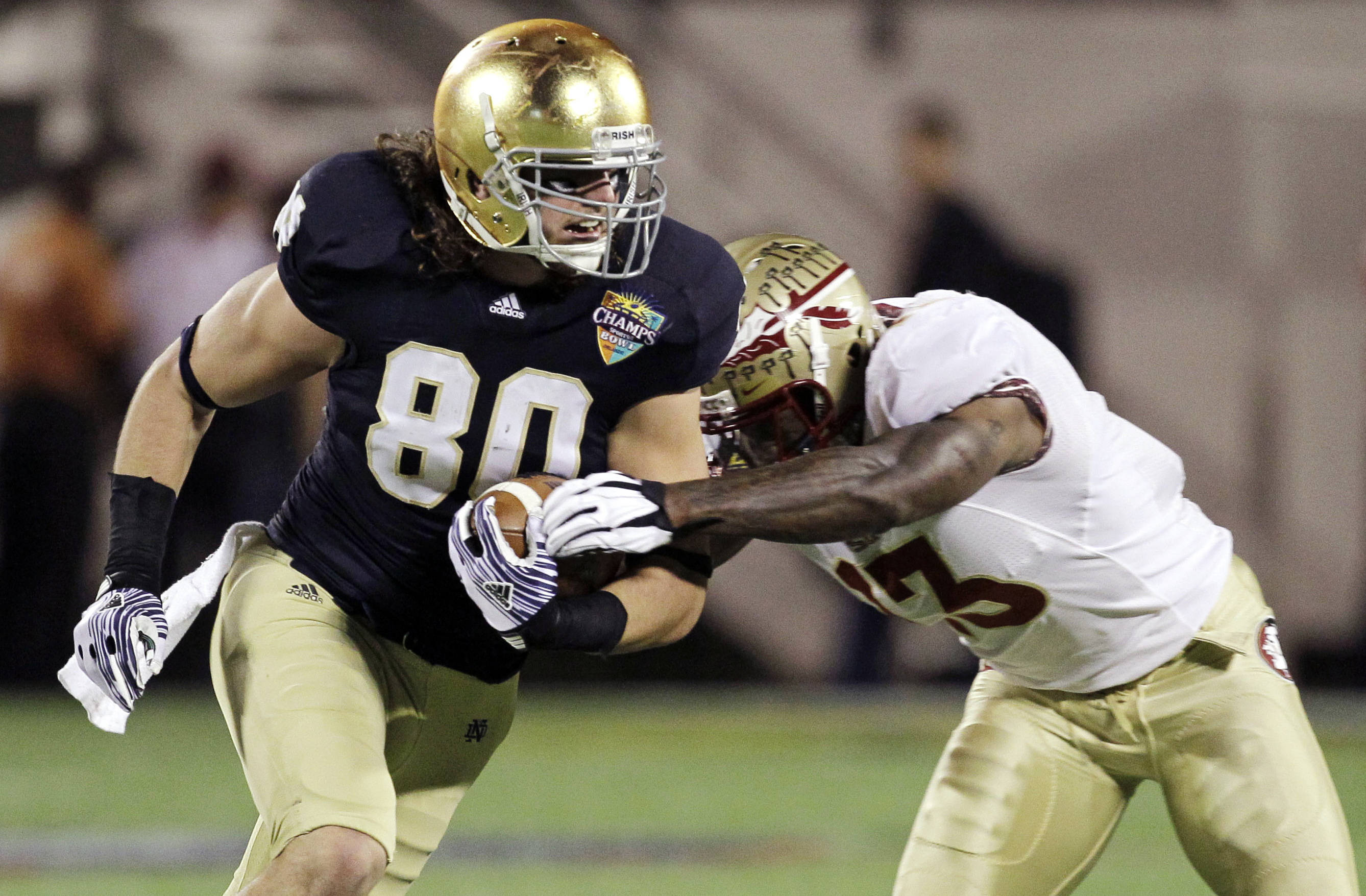 Florida State linebacker Nigel Bradham tries to bring down Notre Dame tight end Tyler Eifert after a reception in the first half of the Champs Sports Bowl. (AP Photo/John Raoux)