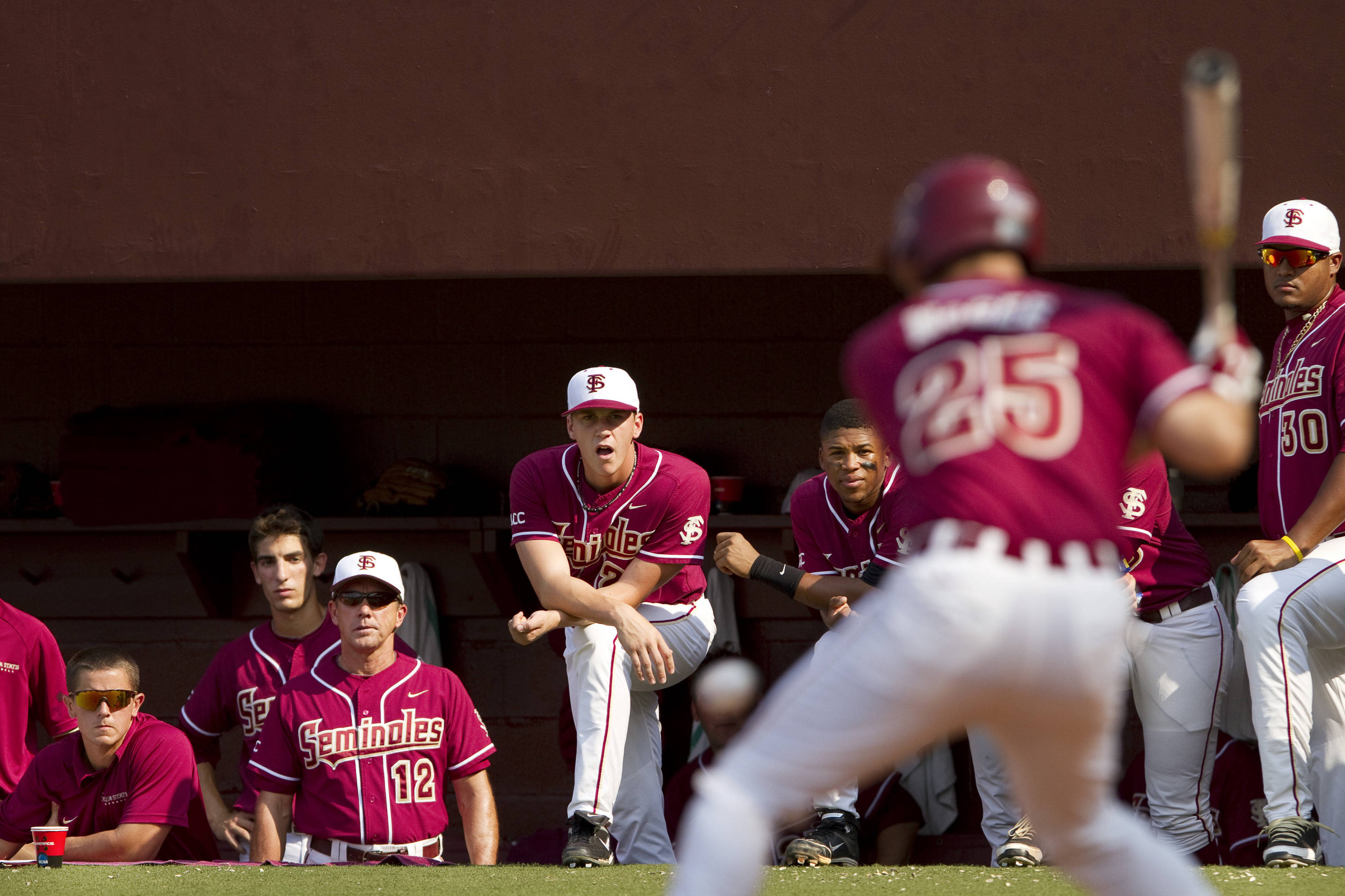 Teammates watch as Mike McGee (25) bats in the game against Texas A&M.