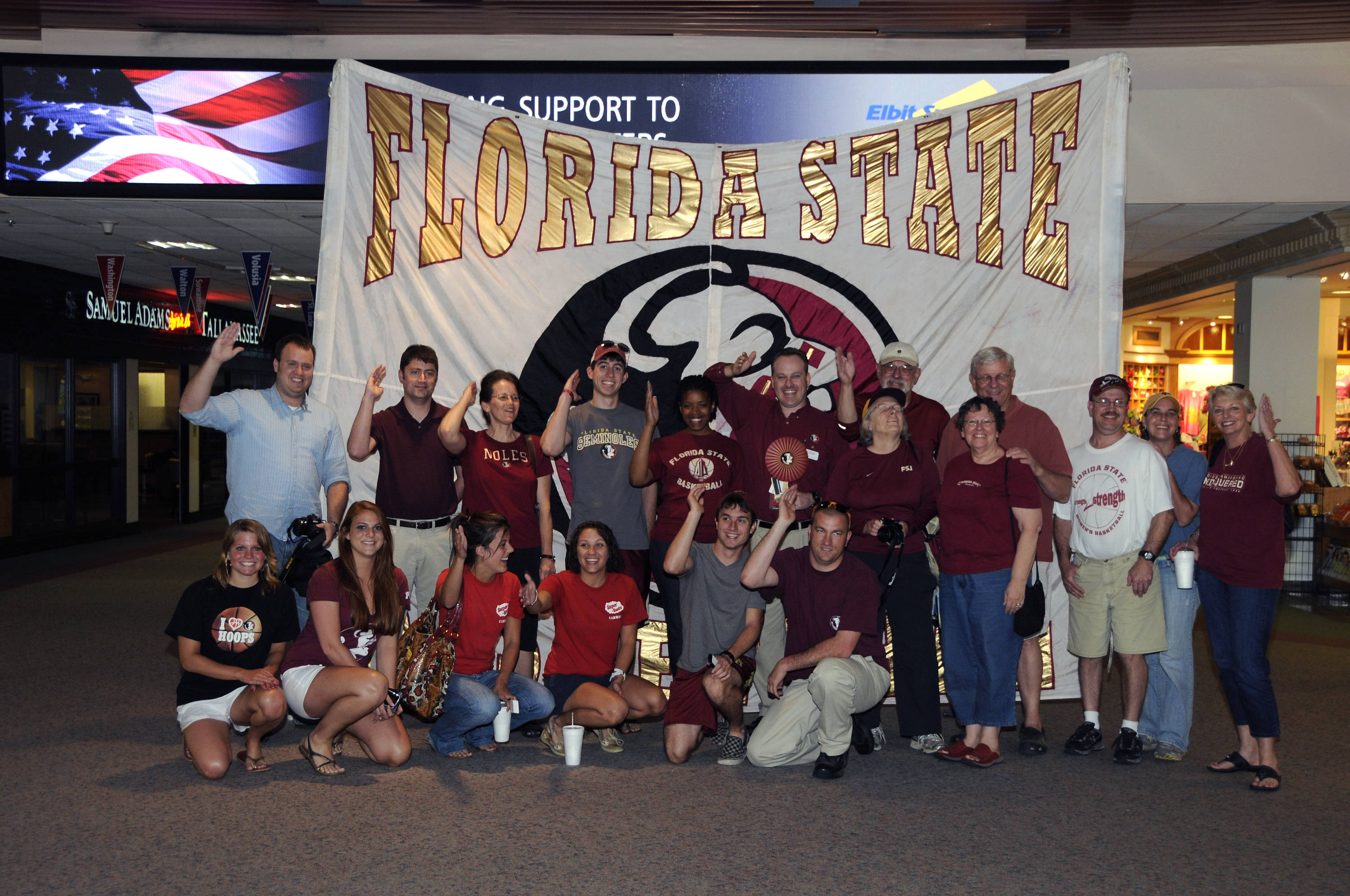 Seminole fans pose in front of a banner as they wait for the men's basketball team to arrive at the Tallahassee Airport