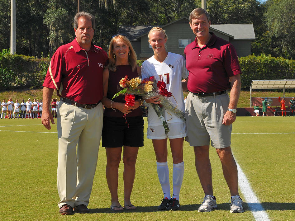 Head coach Mark Krikorian and Director of Athletics Randy Spetman with Ella Stephan and her mom on senior day.
