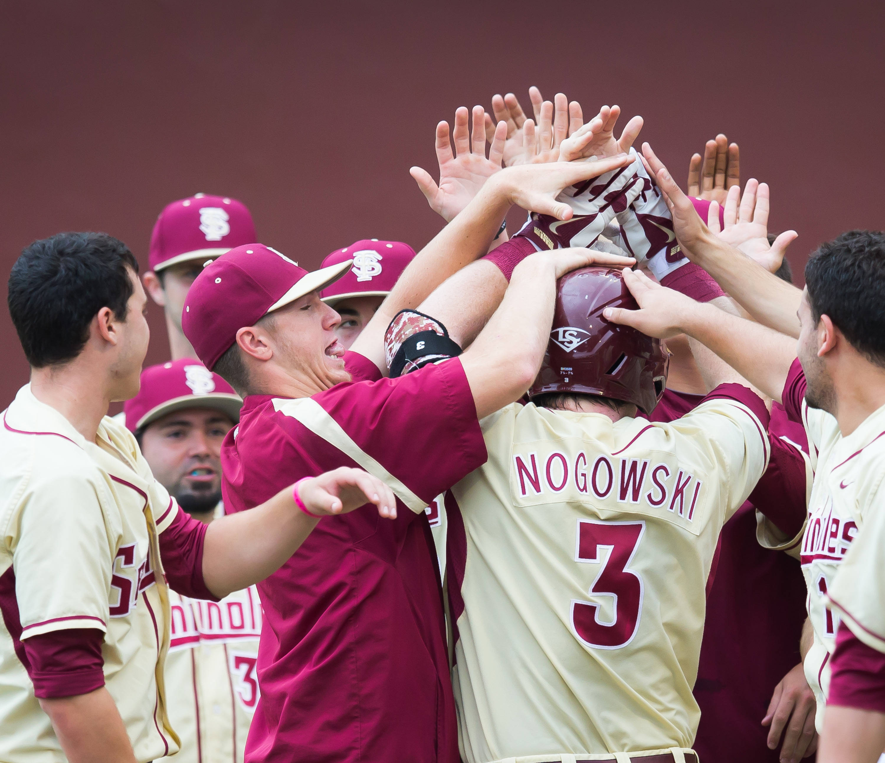 John Nogowski (3) is mobbed by his teammates after his 1st inning homer.