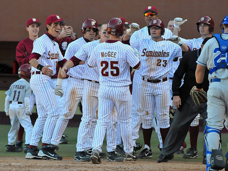 Mike McGee celebrates with teams after crossing home plate.