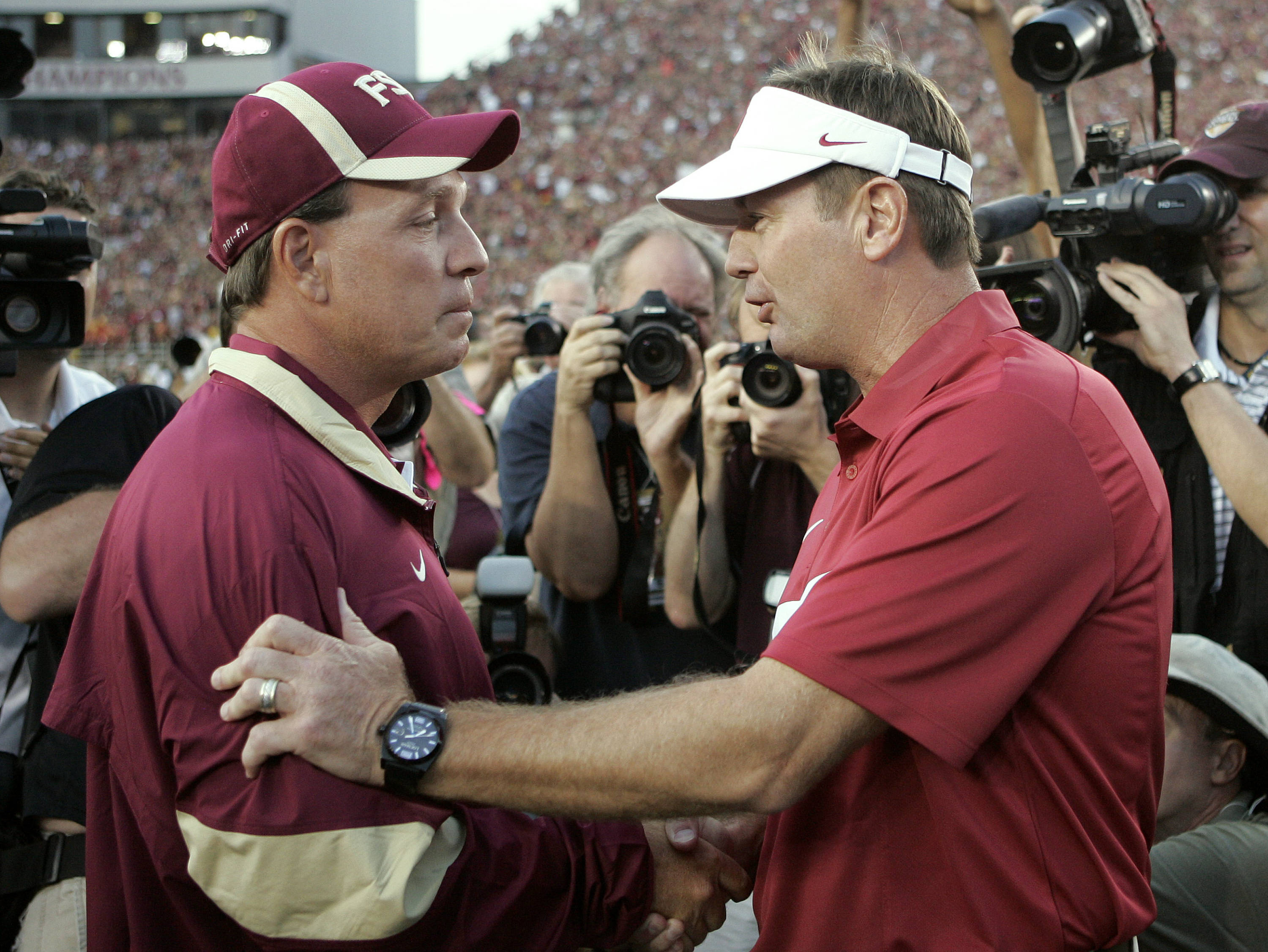 Oklahoma head coach Bob Stoops, right, talks to Florida State head coach Jim Fisher before the start of an NCAA college football game, Saturday, Sept. 17, 2011, in Tallahassee, Fla. (AP Photo/Steve Cannon)