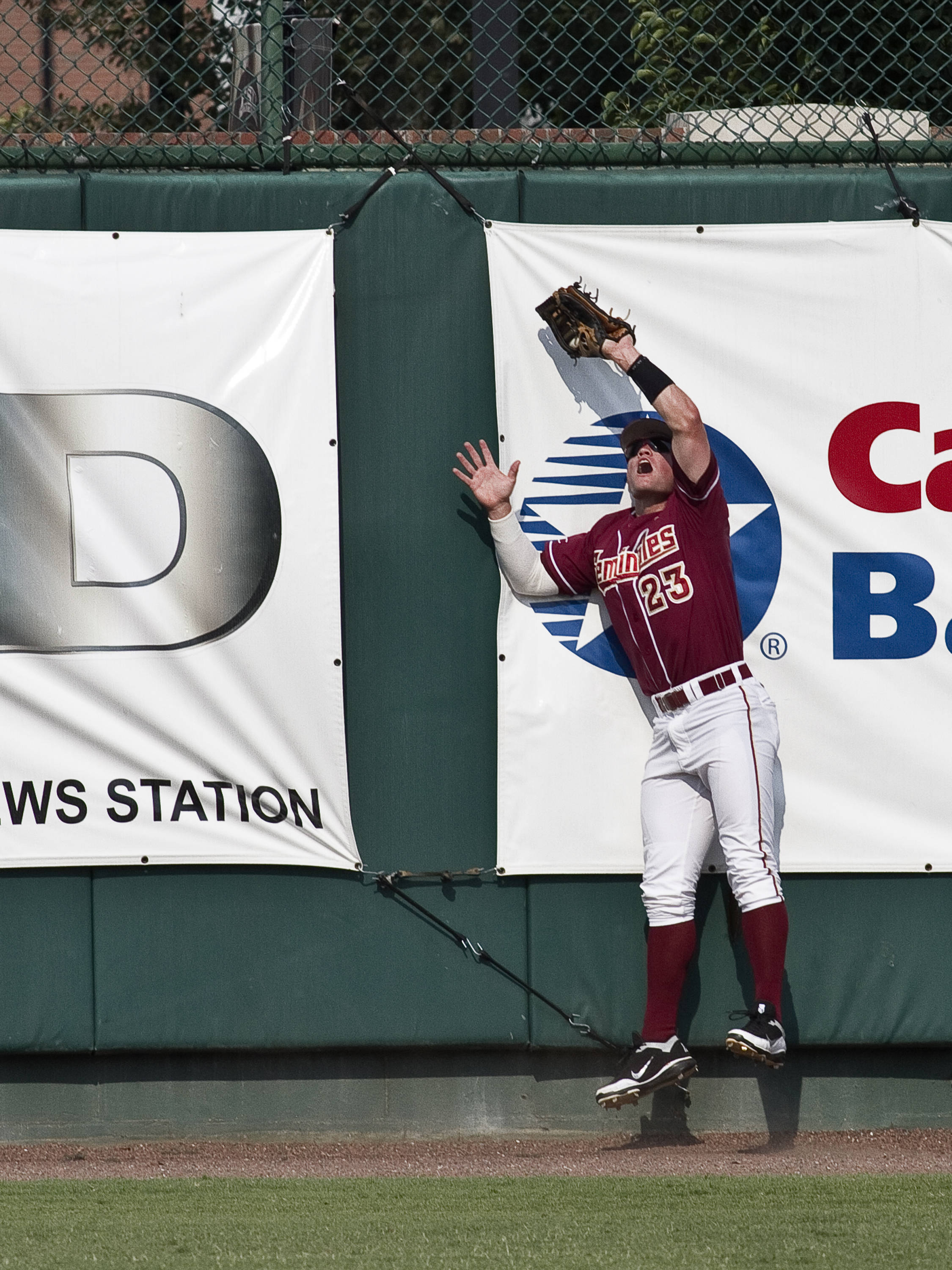 Outfielder James Ramsey (23) going up against the wall  to make a catch