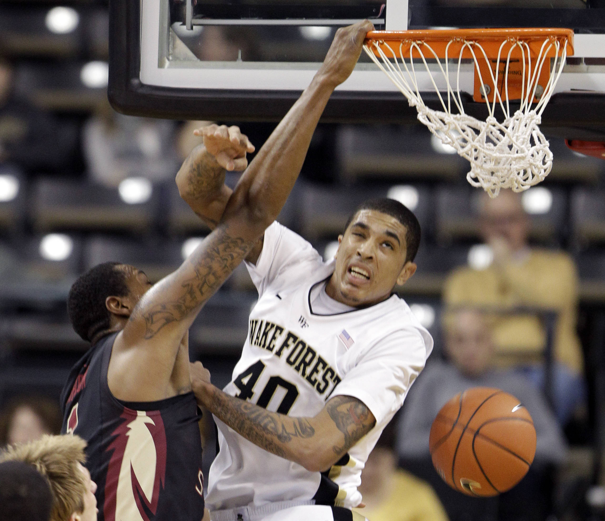 Florida State's Xavier Gibson, left, dunks over Wake Forest's Ty Walker. (AP Photo/Chuck Burton)