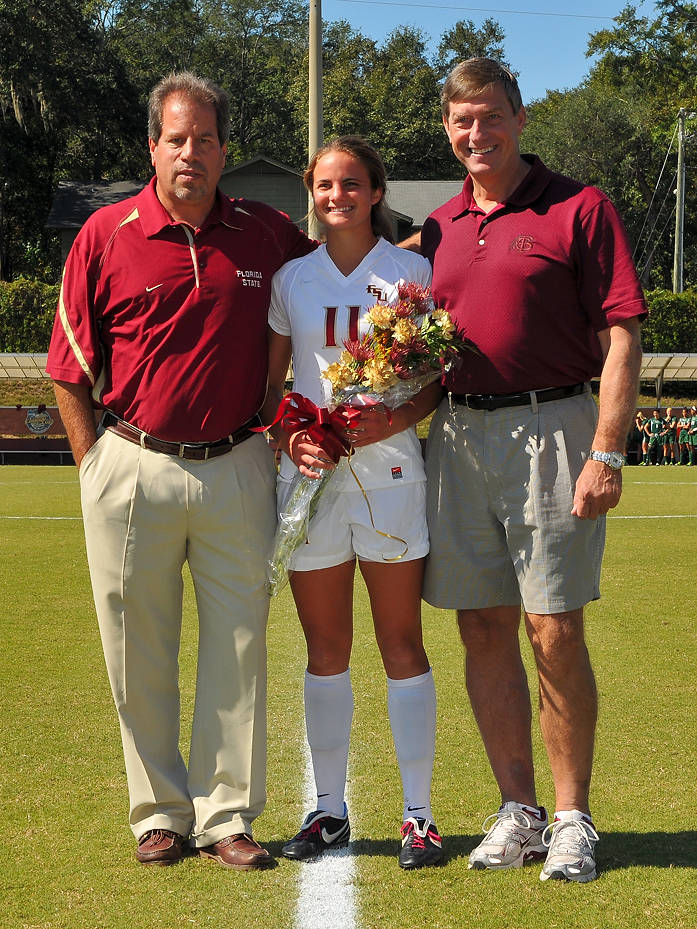 Head coach Mark Krikorian and Director of Athletics Randy Spetman with Katie Riley on senior day.