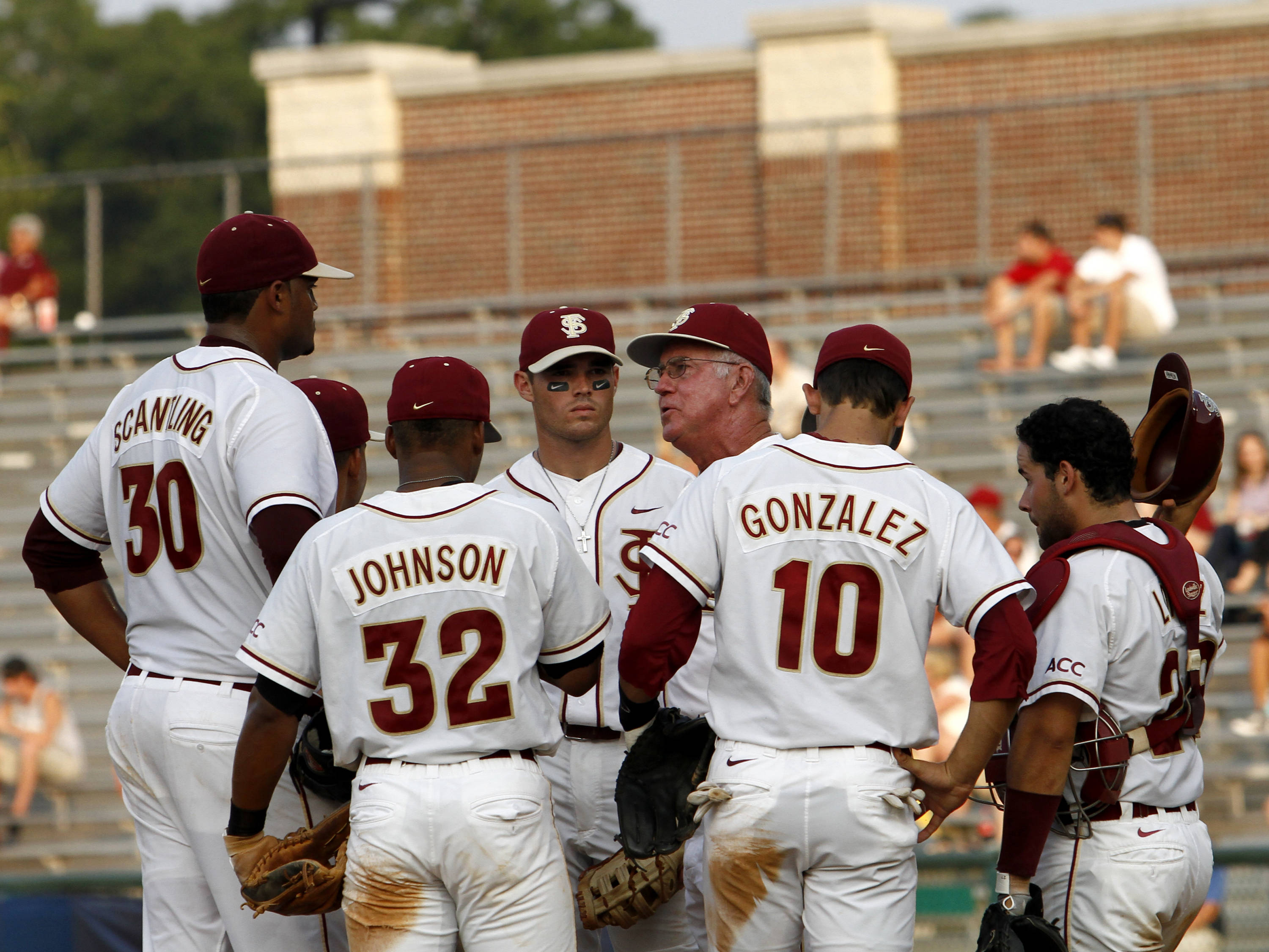 Head Coach Mike Martin with some game discussion with his pitcher Hunter Scantling (30) and his infield.