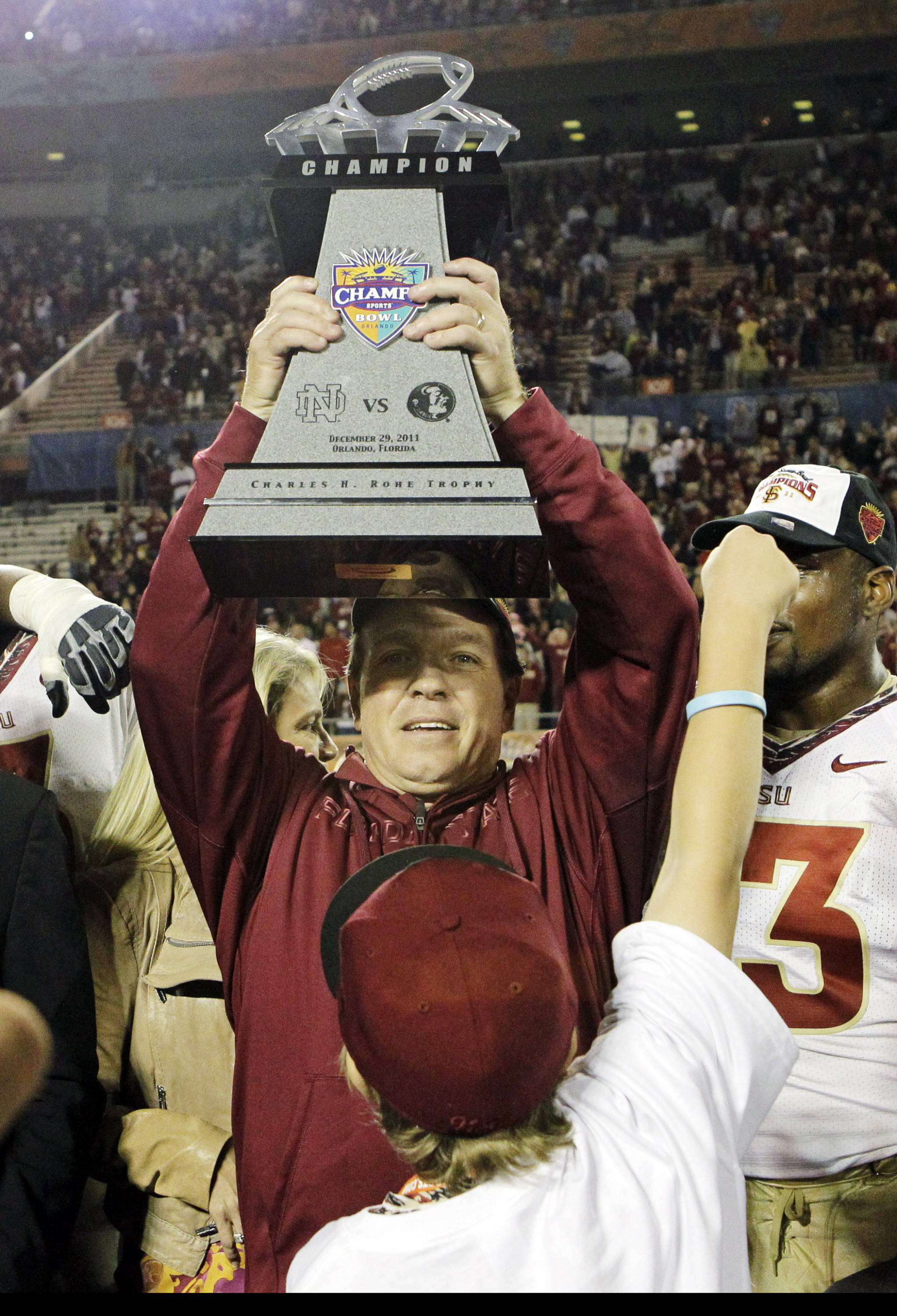 Florida State head coach Jimbo Fisher holds up the championship trophy after defeating Notre Dame 18-14 in the Champs Sports Bowl. (AP Photo/John Raoux)