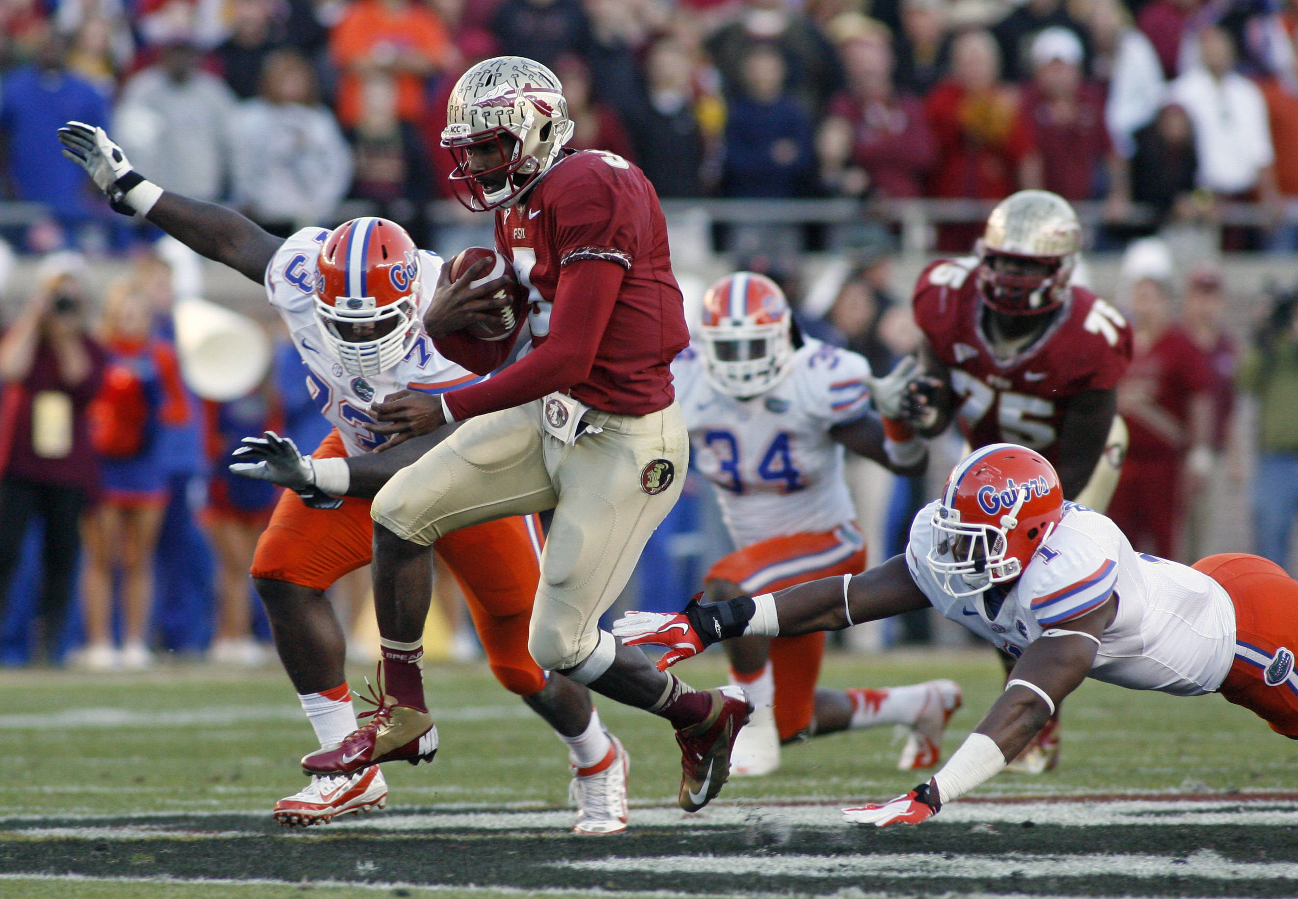 Florida State quarterback EJ Manuel, front center, slips past Florida defensive lineman Sharrif Floyd (73) and linebacker Jon Bostic (1) for a 23-yard run. (AP Photo/Phil Sears)