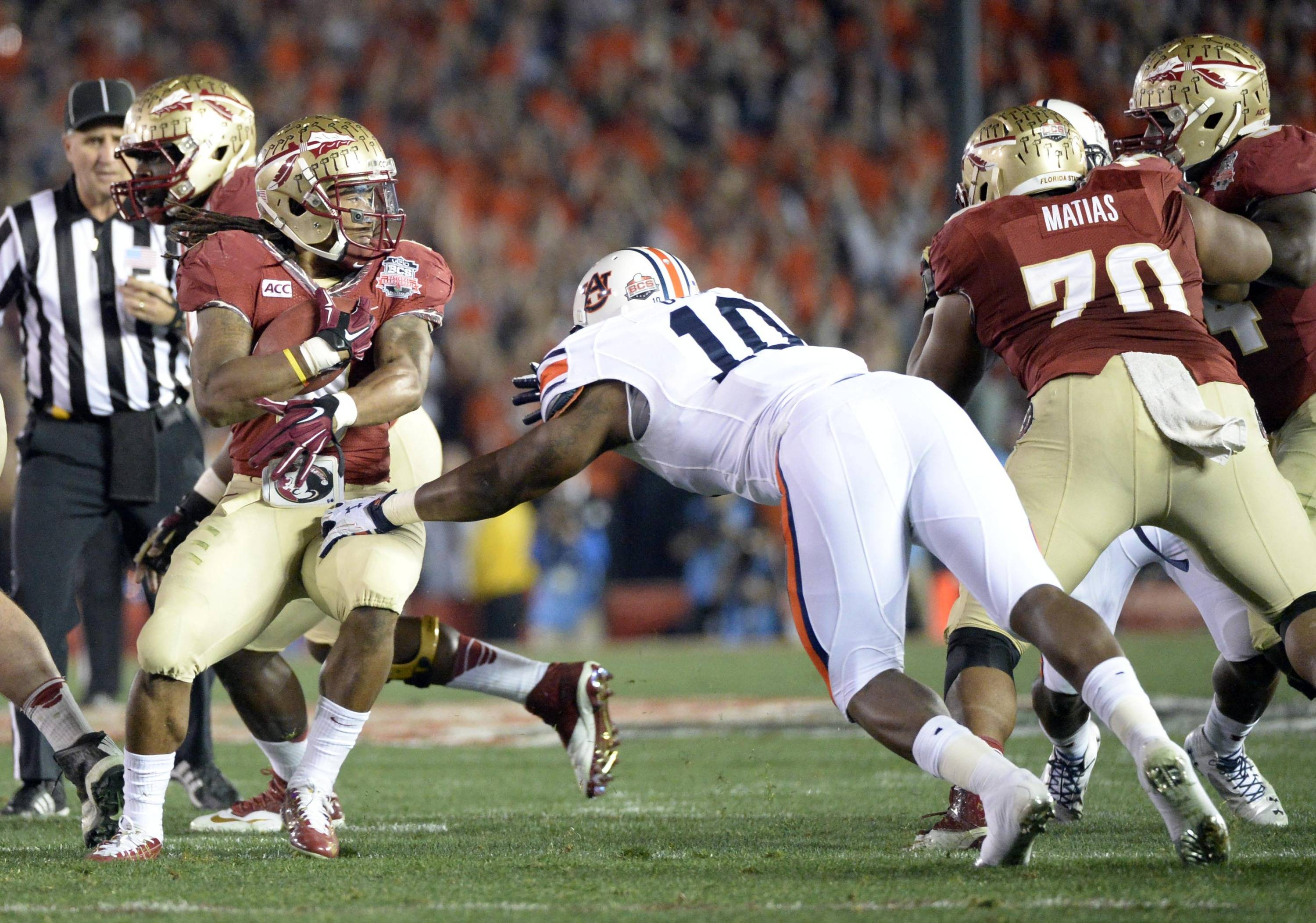 Jan 6, 2014; Pasadena, CA, USA; Auburn Tigers defensive end LaDarius Owens (10) tackles Florida State Seminoles running back Devonta Freeman (8) during the first half of the 2014 BCS National Championship game at the Rose Bowl.  Mandatory Credit: Richard Mackson-USA TODAY Sports