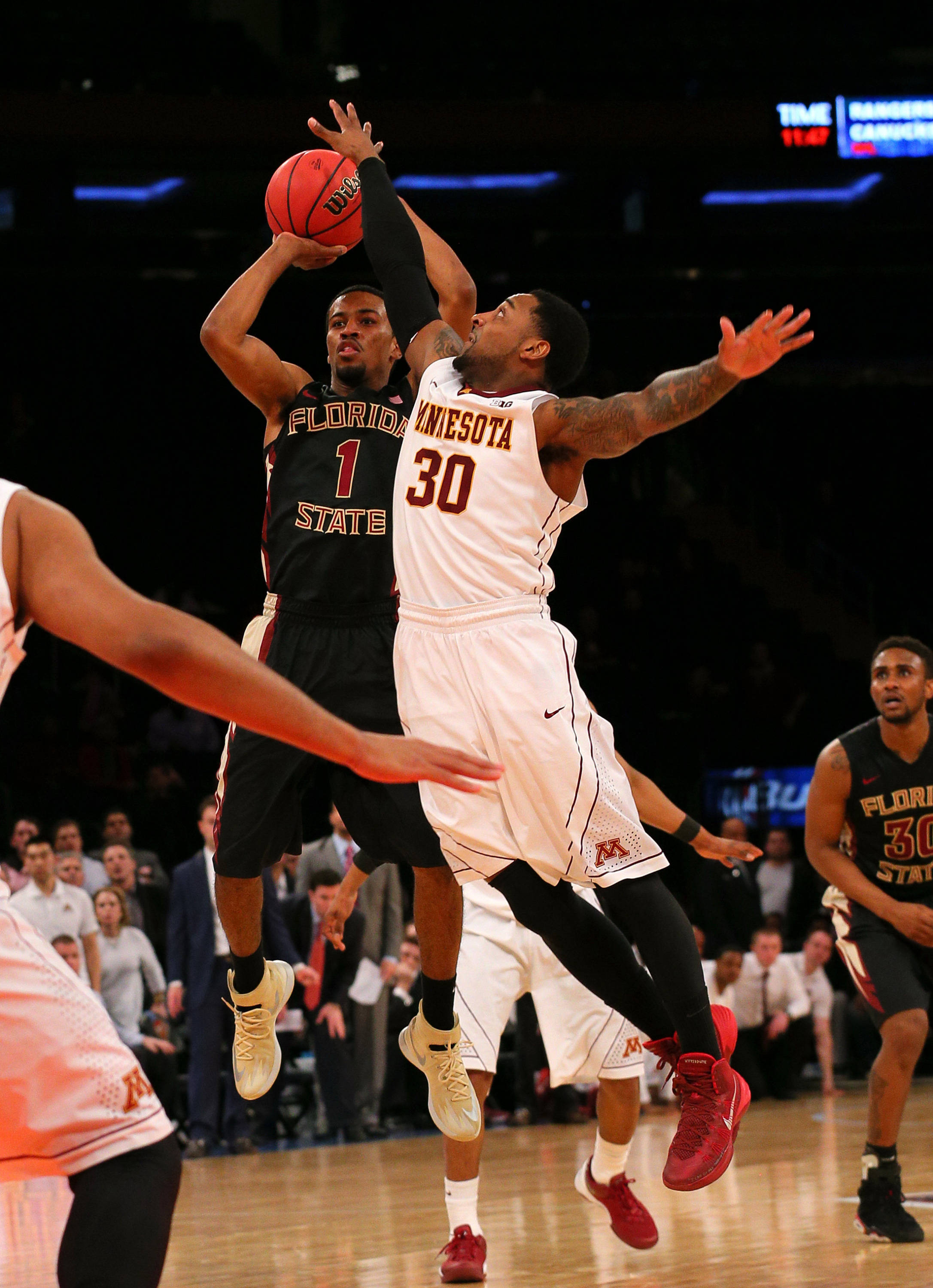 Apr 1, 2014; New York, NY, USA; Florida State Seminoles guard Devon Bookert (1) hits a game tying three-point shot defended by Minnesota Golden Gophers guard Malik Smith (30) during the second half at Madison Square Garden. The Minnesota Golden Gophers defeated the Florida State Seminoles 67-64 in overtime. Mandatory Credit: Adam Hunger-USA TODAY Sports