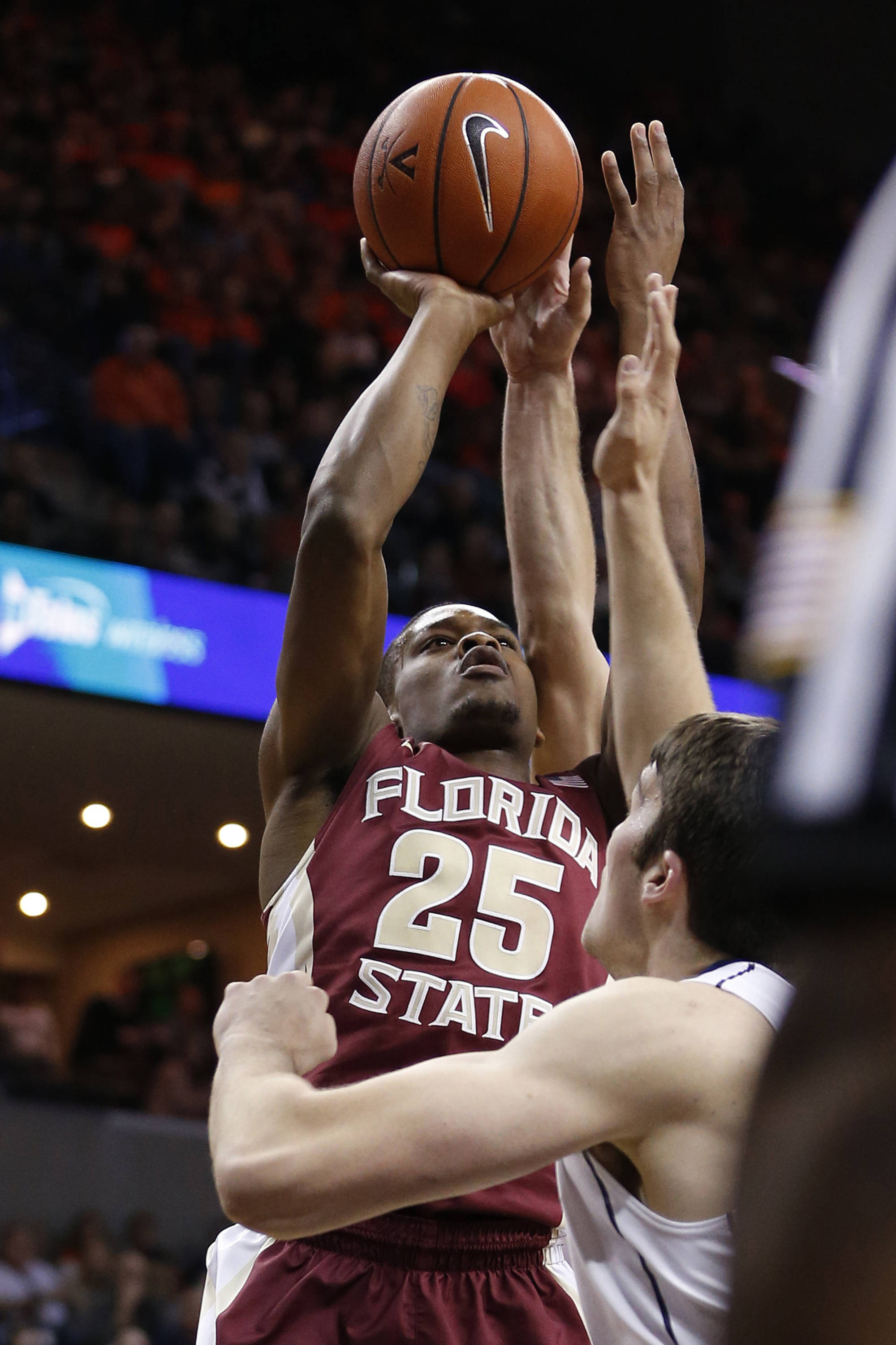 Jan 18, 2014; Charlottesville, VA, USA; Florida State Seminoles guard Aaron Thomas (25) shoots the ball as Virginia Cavaliers forward/center Mike Tobey (10) defends in the first half at John Paul Jones Arena. Mandatory Credit: Geoff Burke-USA TODAY Sports