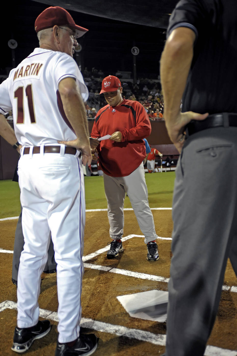 Head coach Mike Martin meets at the mound with Marist head coach Dennis Healy