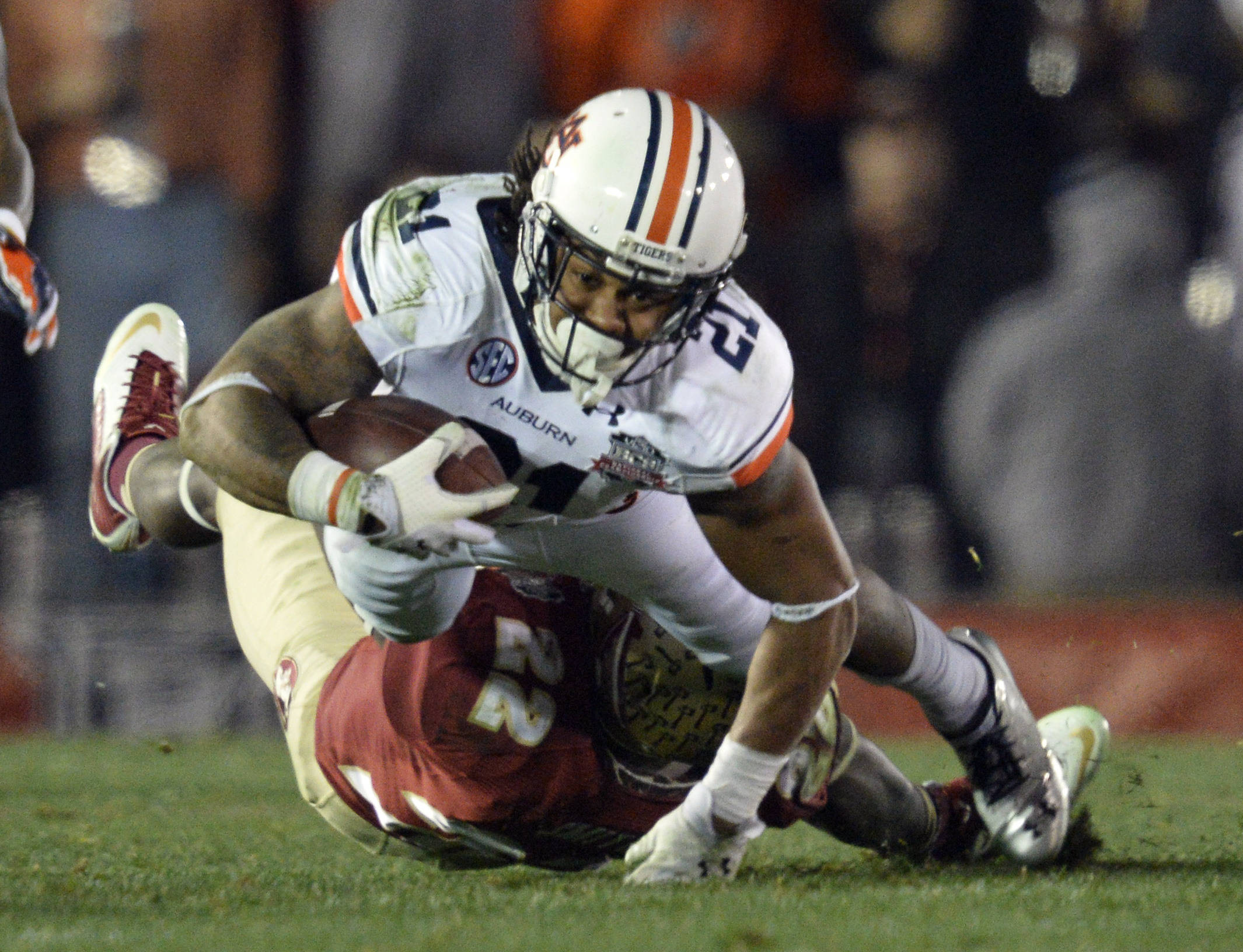 Jan 6, 2014; Pasadena, CA, USA; Auburn Tigers running back Tre Mason (21) is tackled by Florida State Seminoles linebacker Telvin Smith (22) during the first half of the 2014 BCS National Championship game at the Rose Bowl.  Mandatory Credit: Robert Hanashiro-USA TODAY Sports