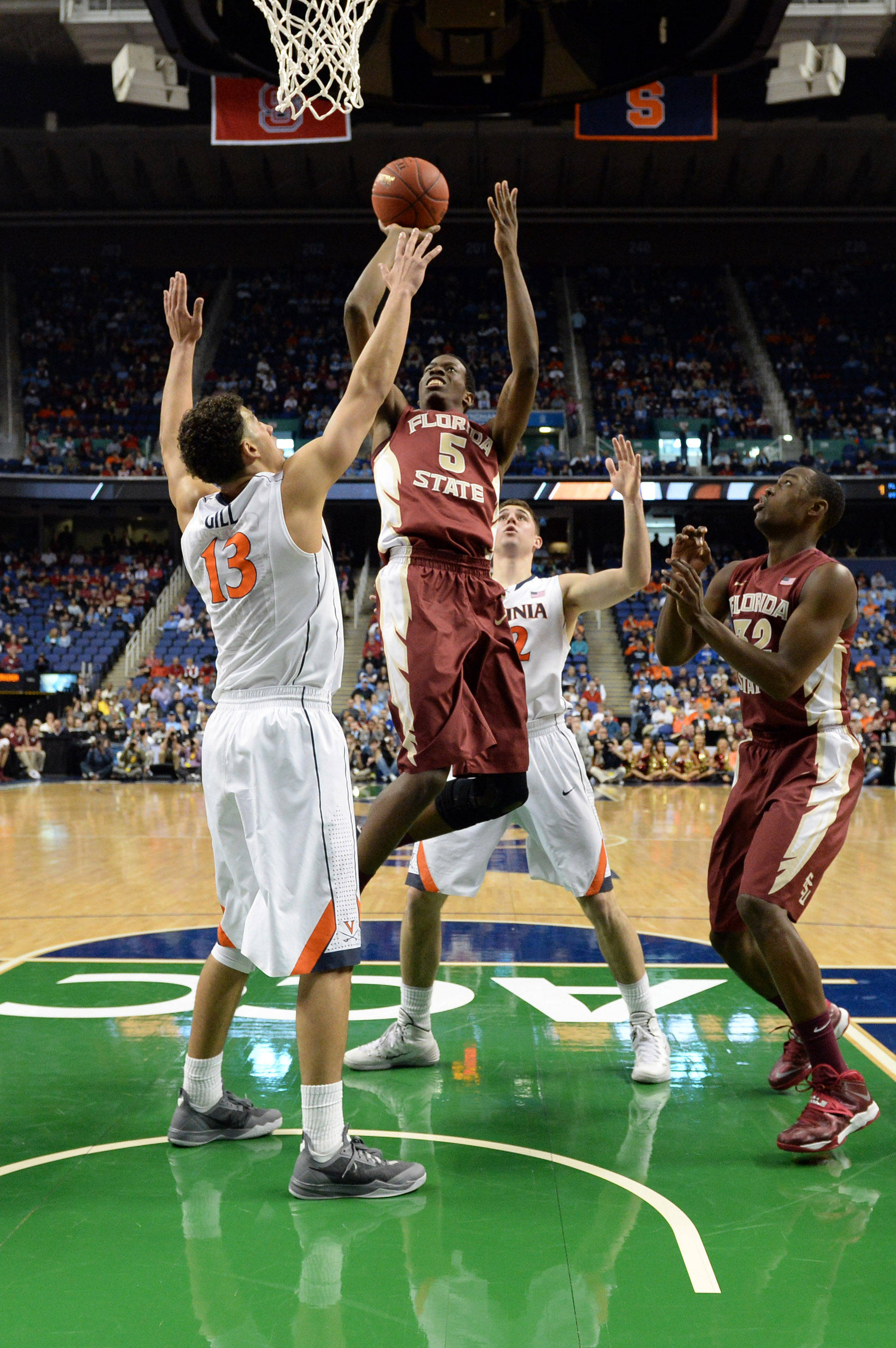 Mar 14, 2014; Greensboro, NC, USA; Florida State Seminoles forward Jarquez Smith (5) drives to the basket against Virginia Cavaliers forward Anthony Gill (13) in the quarterfinals of the ACC college basketball tournament at Greensboro Coliseum. Mandatory Credit: John David Mercer-USA TODAY Sports