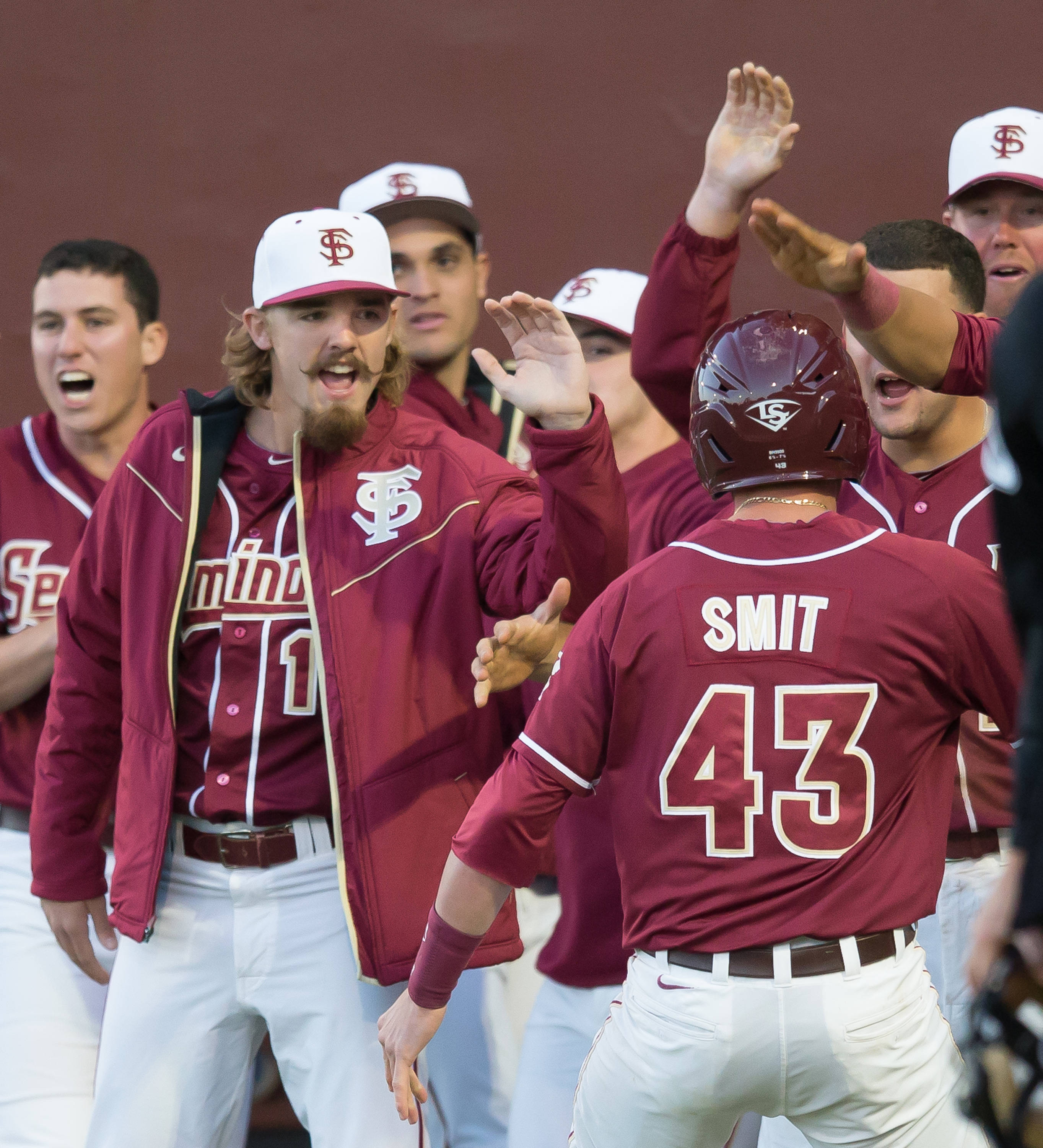Teammates greet Casey Smit (43) after he scores the Noles first run.