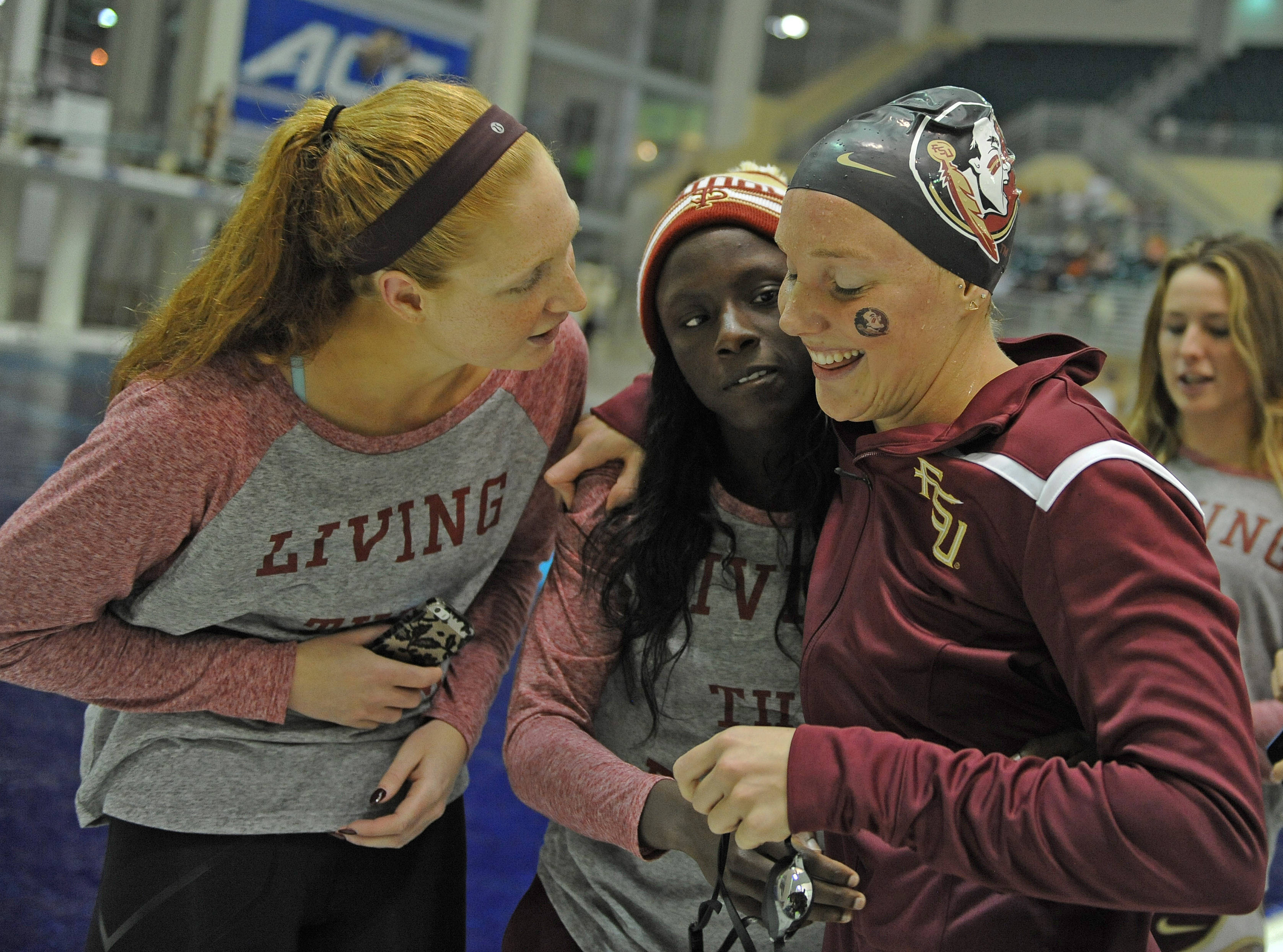 Haley Powell and Alexi Smith hug Kaitlyn Dressel after her race - Mitch White
