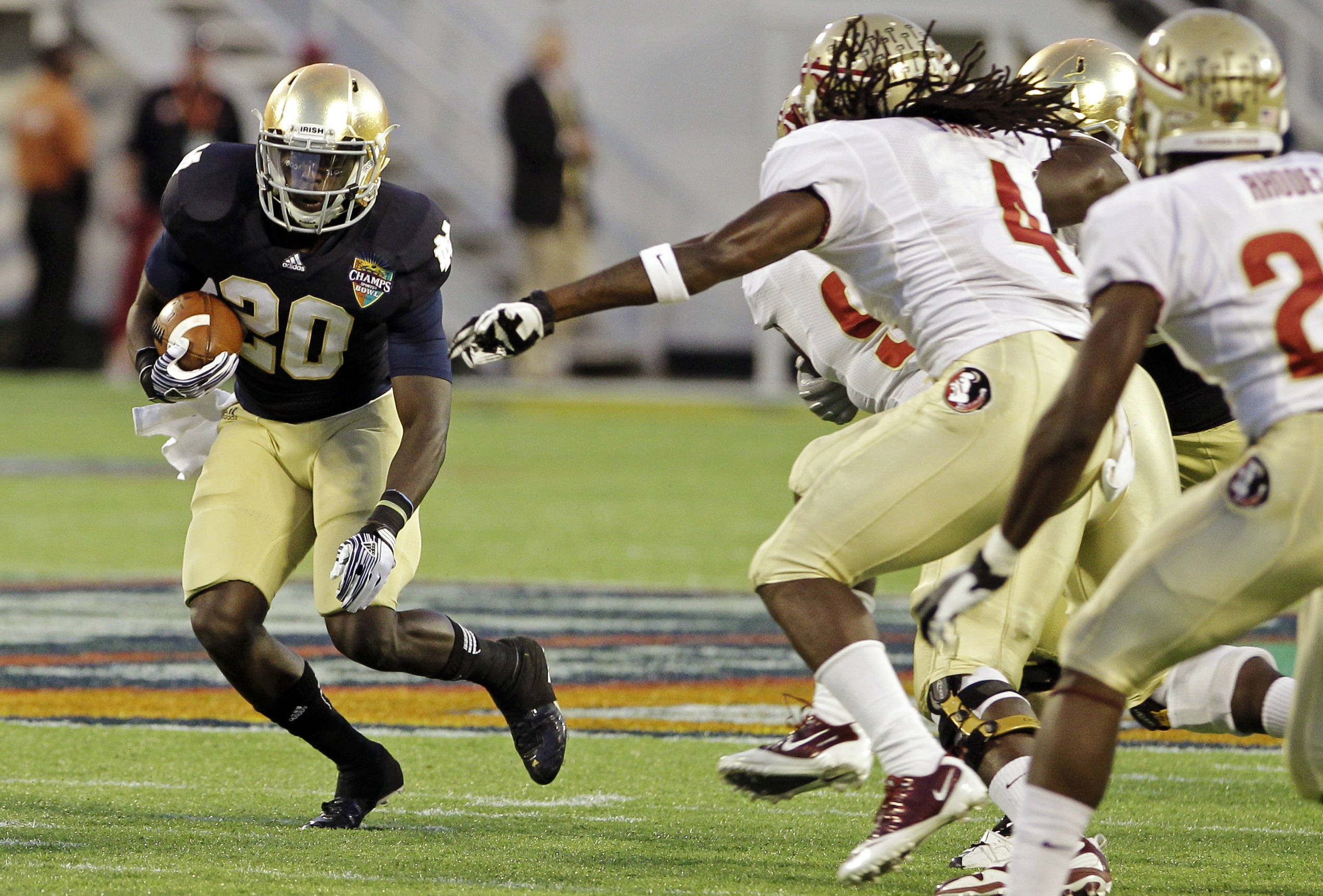 Florida State defenders Terrance Parks (4) and Xavier Rhodes, right, pursue Notre Dame running back Cierre Wood. (AP Photo/John Raoux)