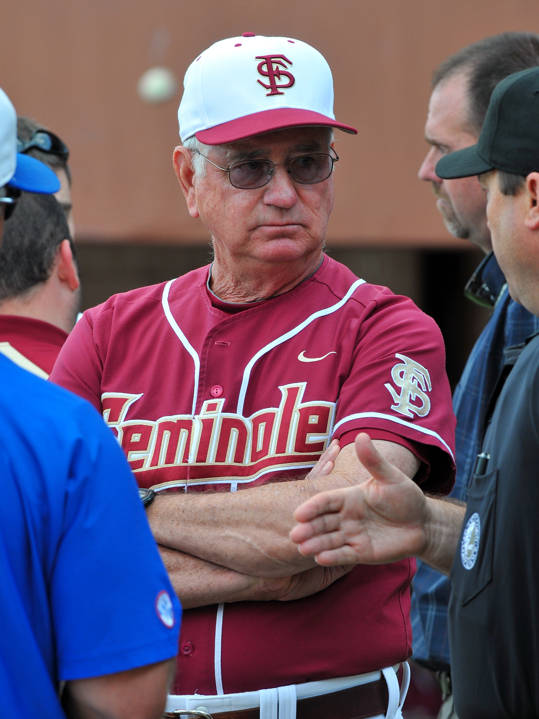 Head coach Mike Martin discuss a game plan following a stadium power outage with umpires and UF head coach Kevin Sullivan.