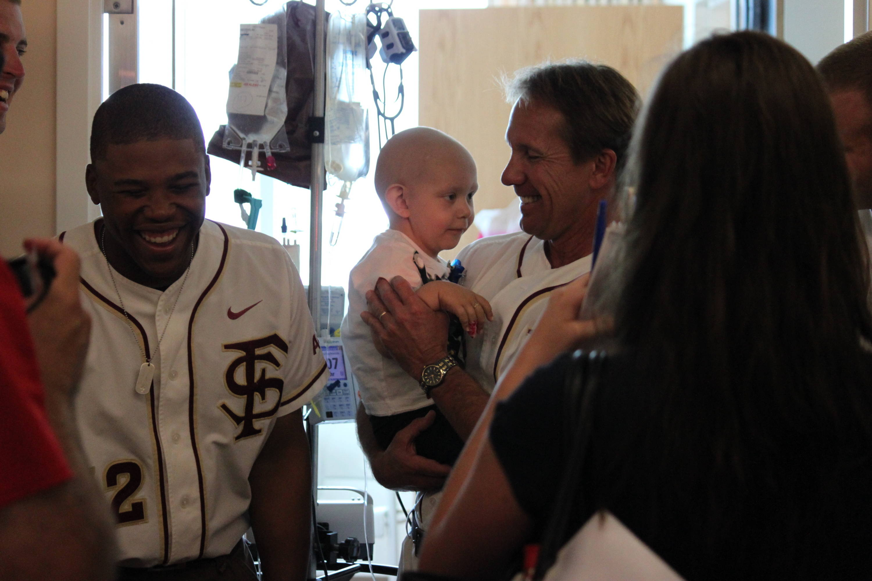 Sherman Johnson and associate head coach Jamey Shouppe making friends with a young Seminole fans during the team's visit to the Children's Hospital